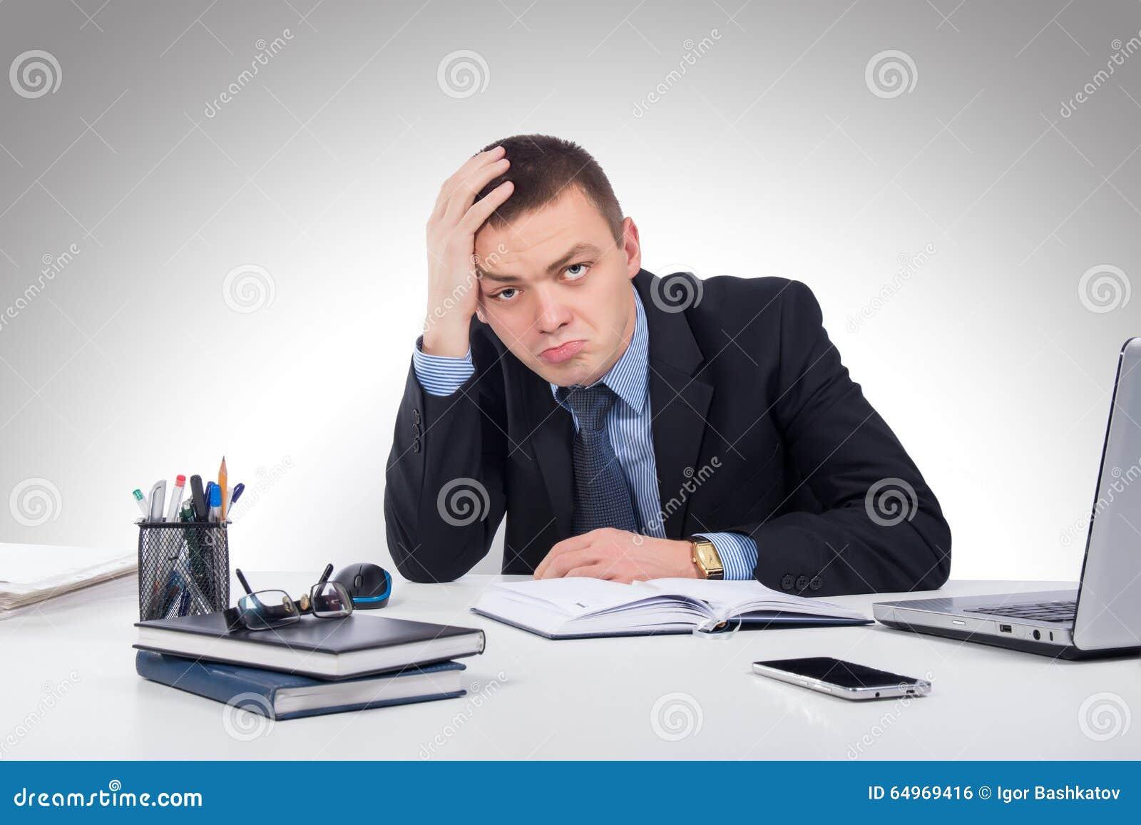 Разочарованный молодой бизнесмен работая на портативном компьютере на offi