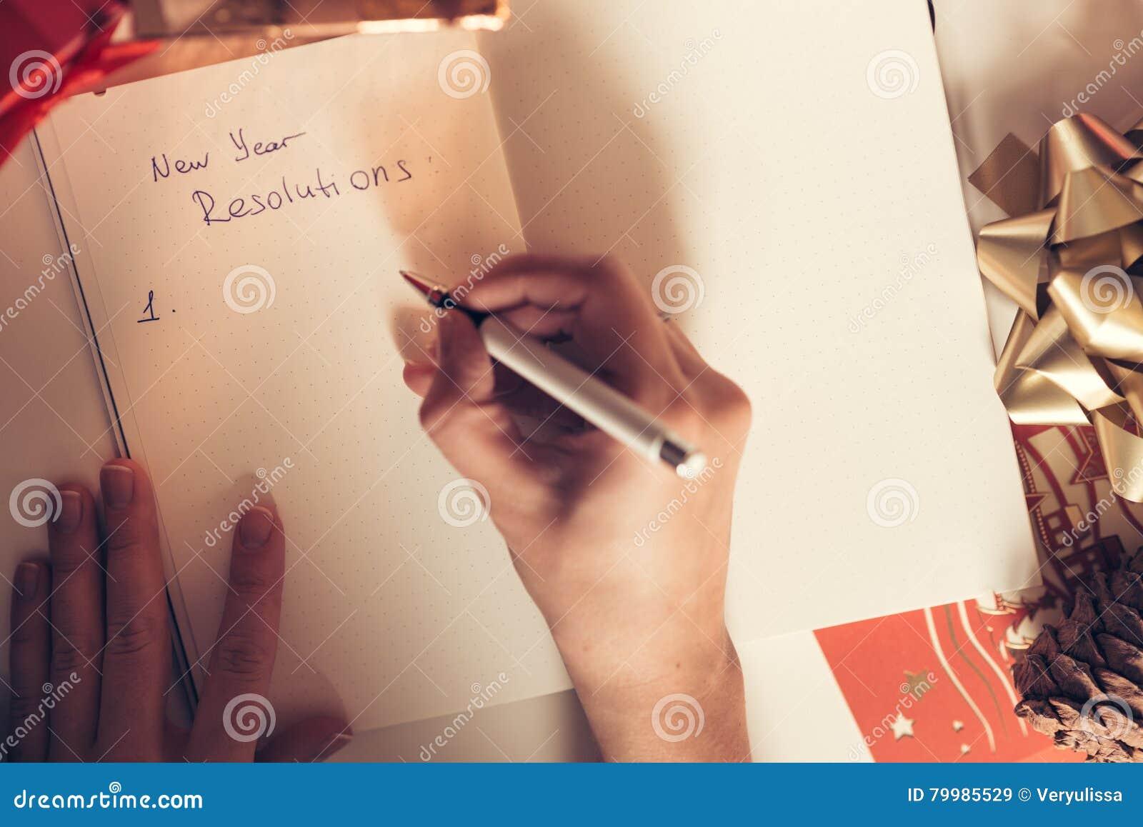 Разрешения Нового Года написанные с рукой на тетради с deco Новых Годов