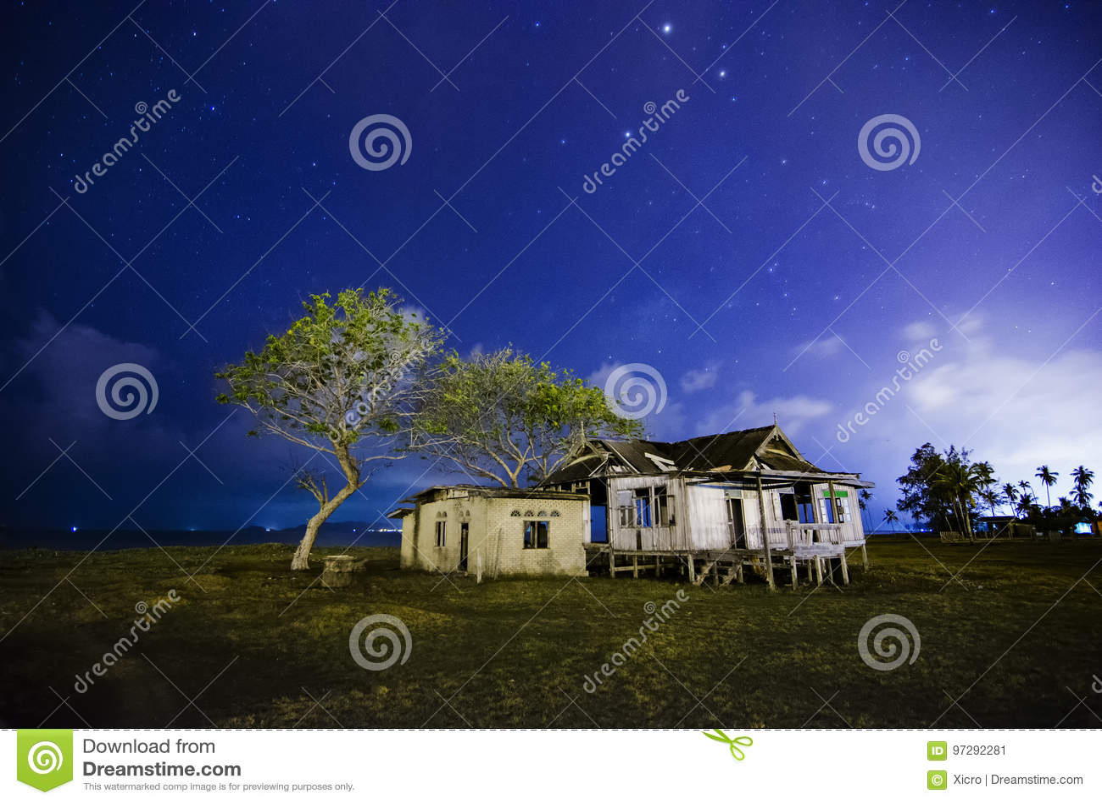 Разрушанный дом развязности деревянный на ноче с предпосылкой звезды и облачного неба