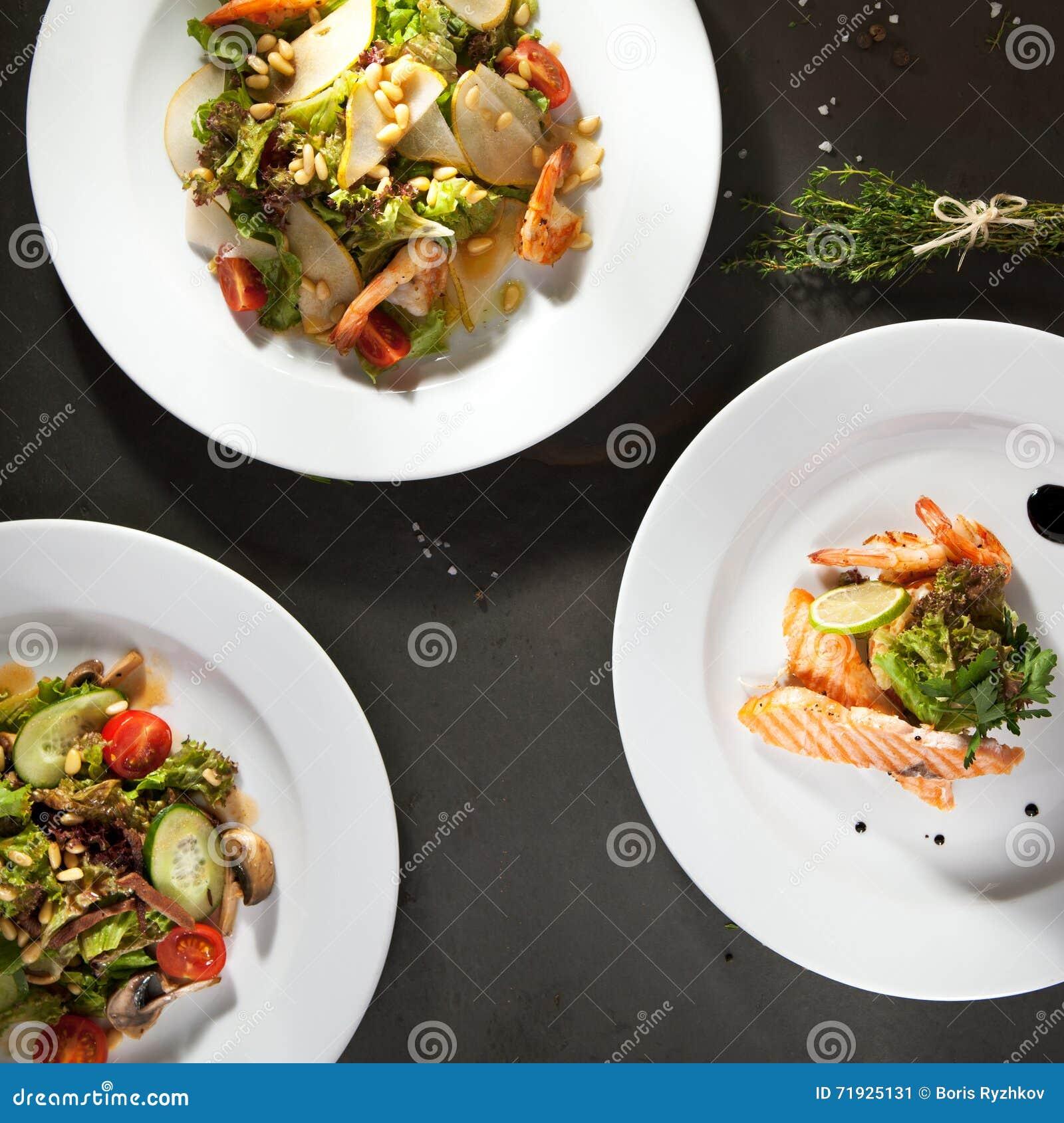 Различный салат на черной каменной предпосылке