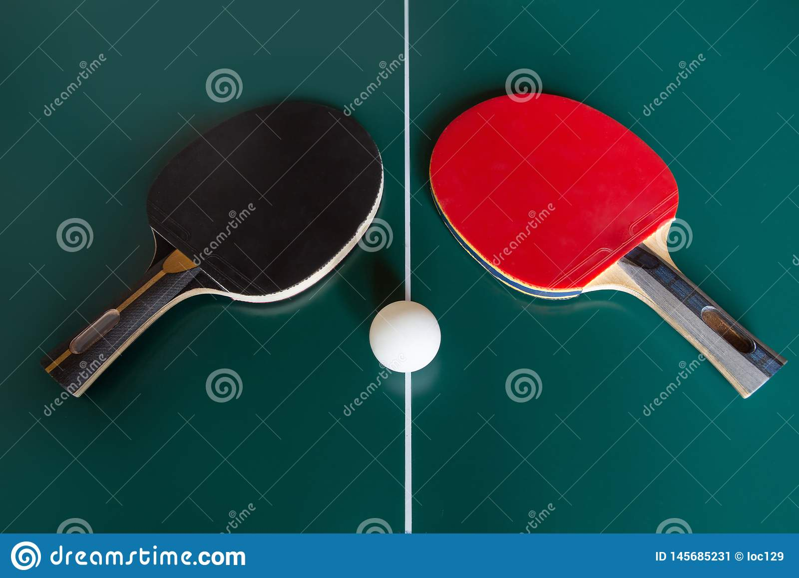 2 ракетки пингпонга и шарик на зеленой таблице