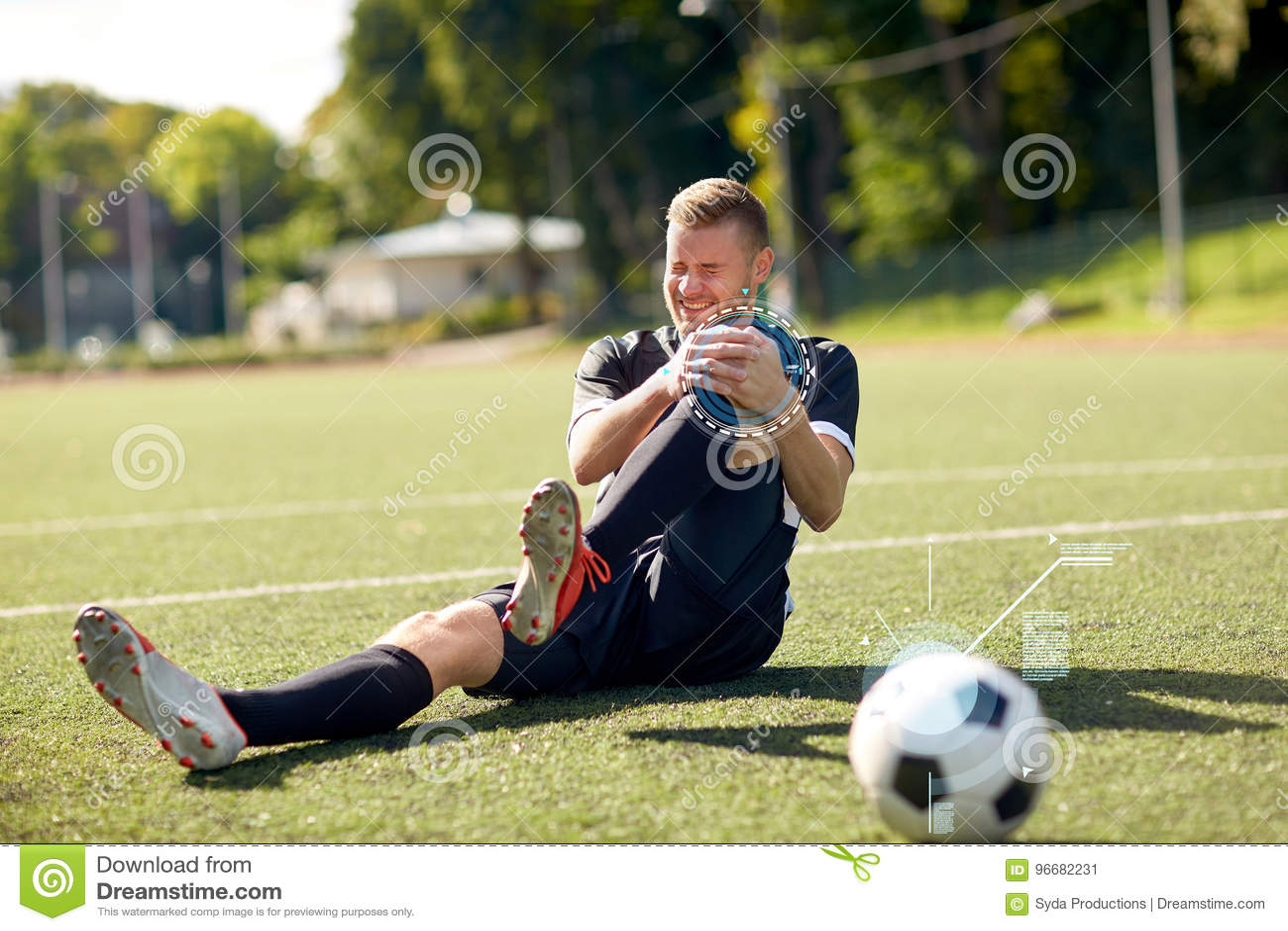 Раненый футболист с шариком на футбольном поле