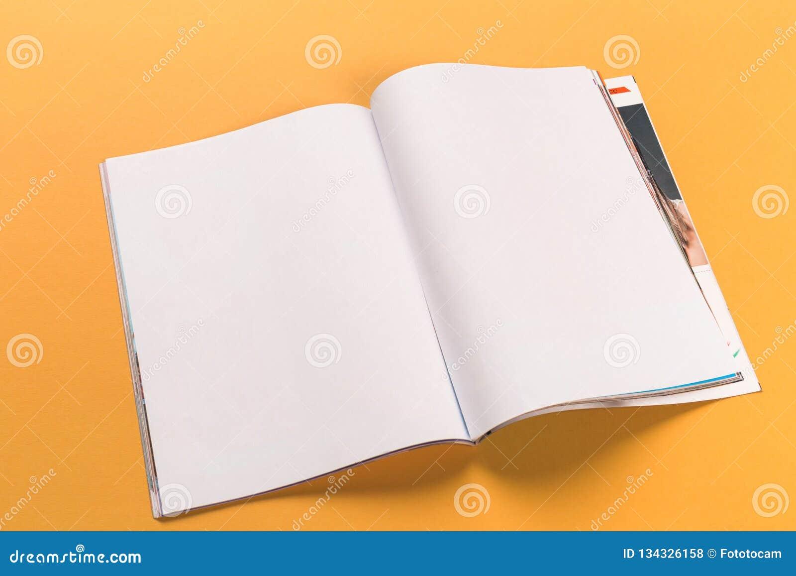 Раскрытый модель-макет журнала на оранжевой предпосылке