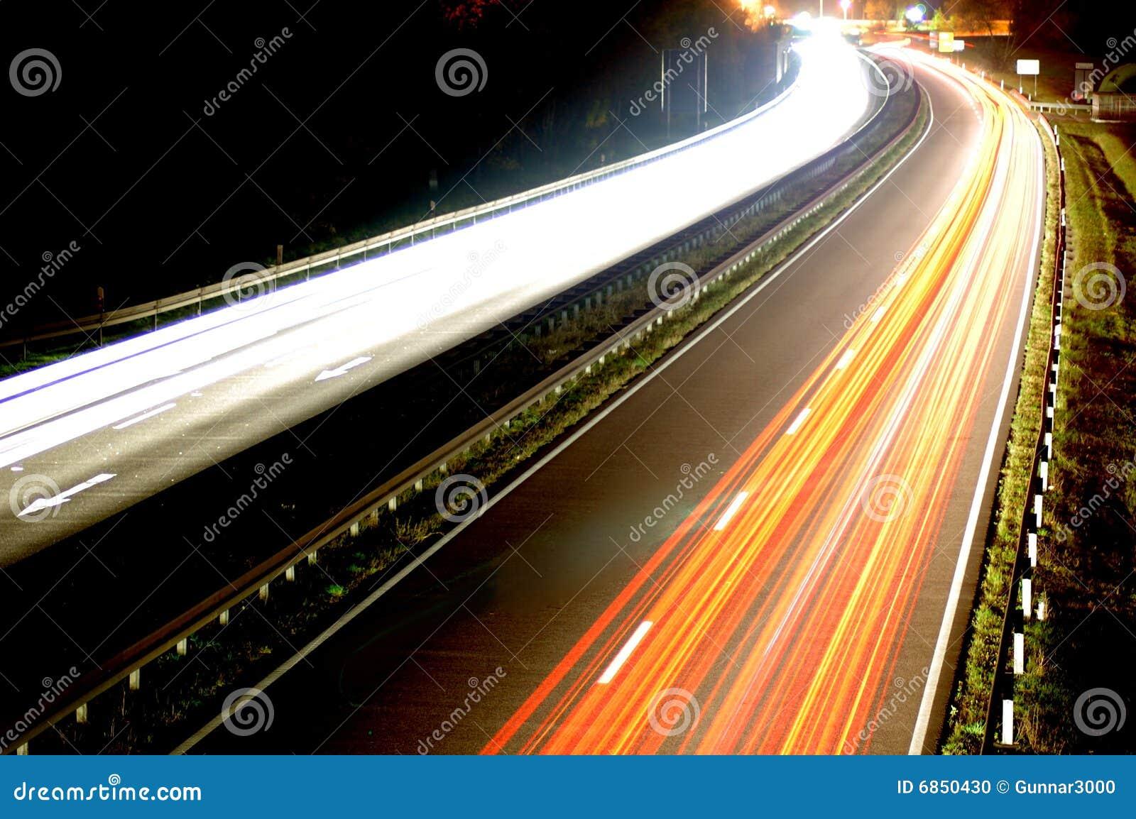 расплывчатый автомобиль освещает движение дороги ночи