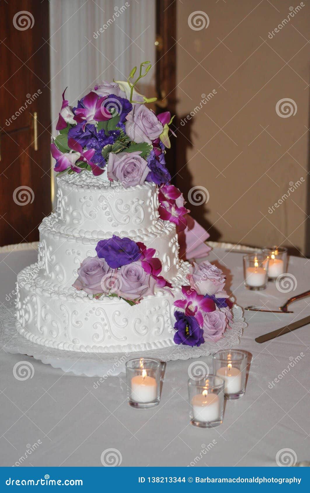 Расположенный ярусами свадебный пирог со свечами, розами, и цветками