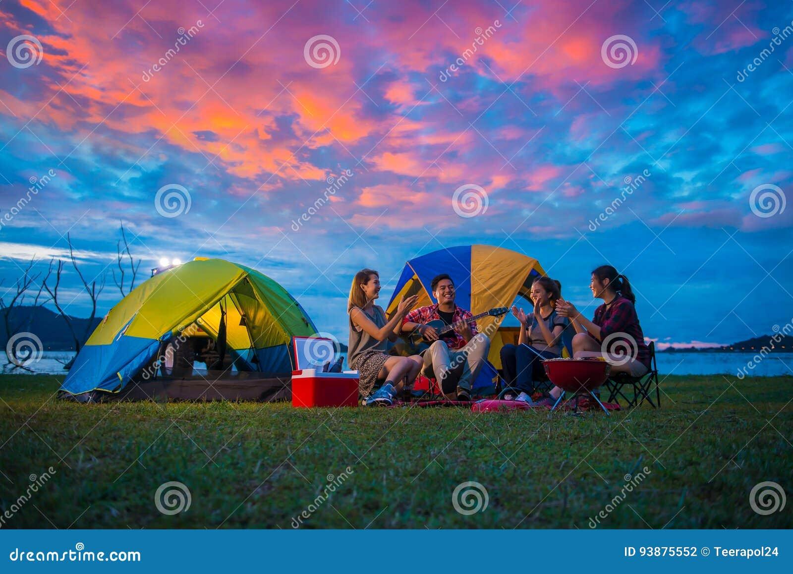Располагаться лагерем счастливых азиатских молодых путешественников на озере