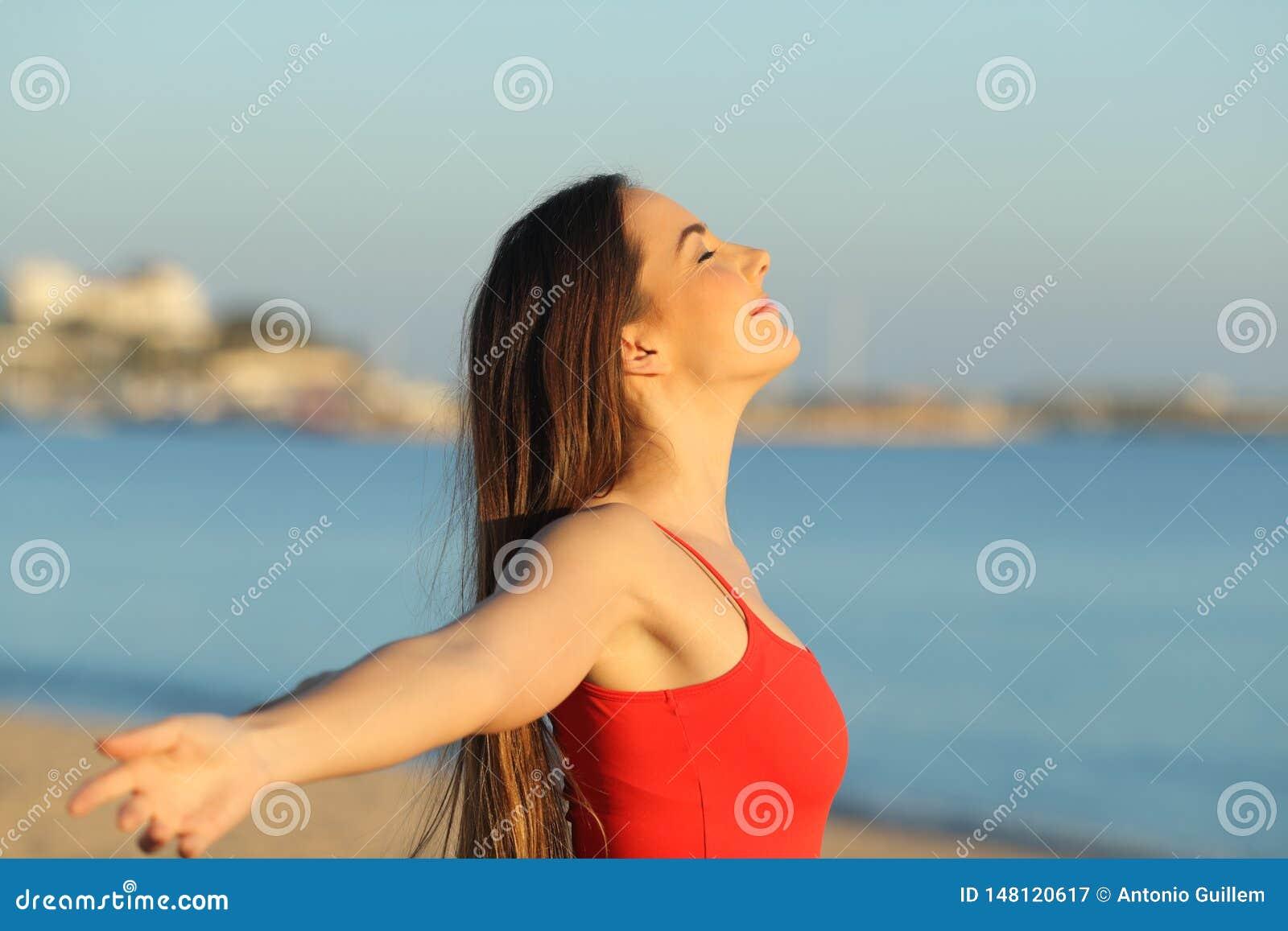 Расслабленная девушка в красном дыша свежем воздухе на пляже