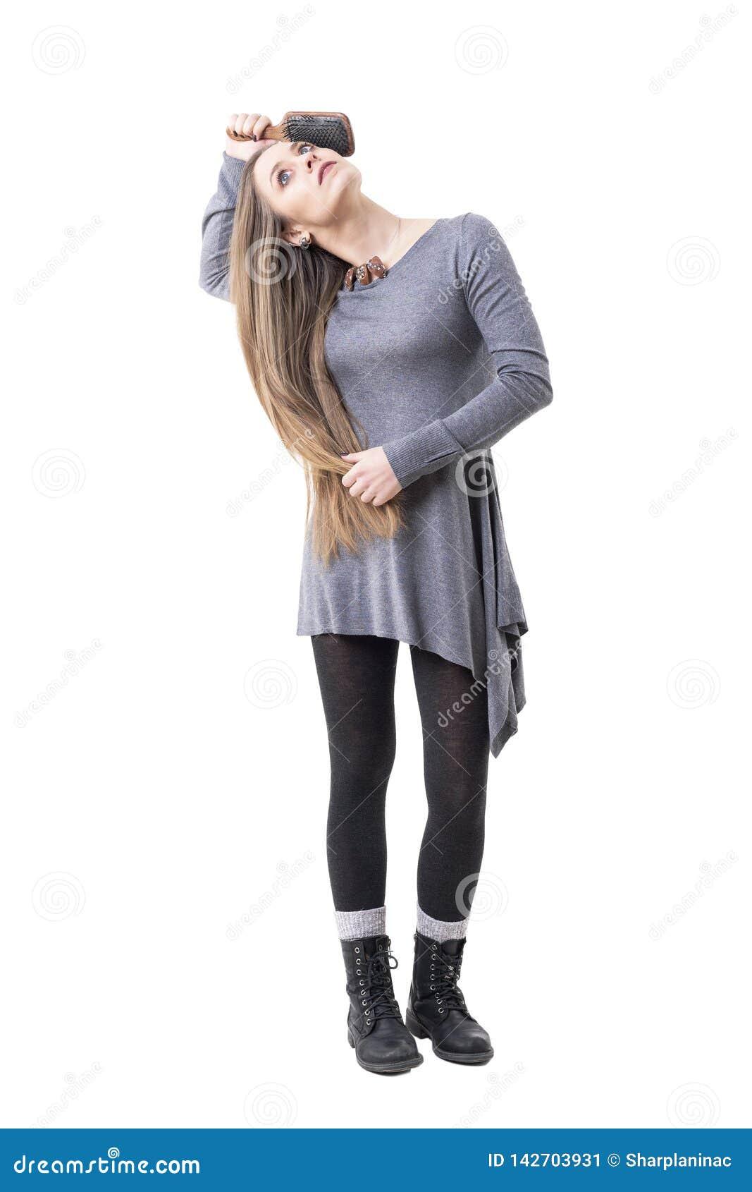 Расслабленная молодая женщина делая ежедневный режим чистя ее длинные белокурые ровные волосы щеткой