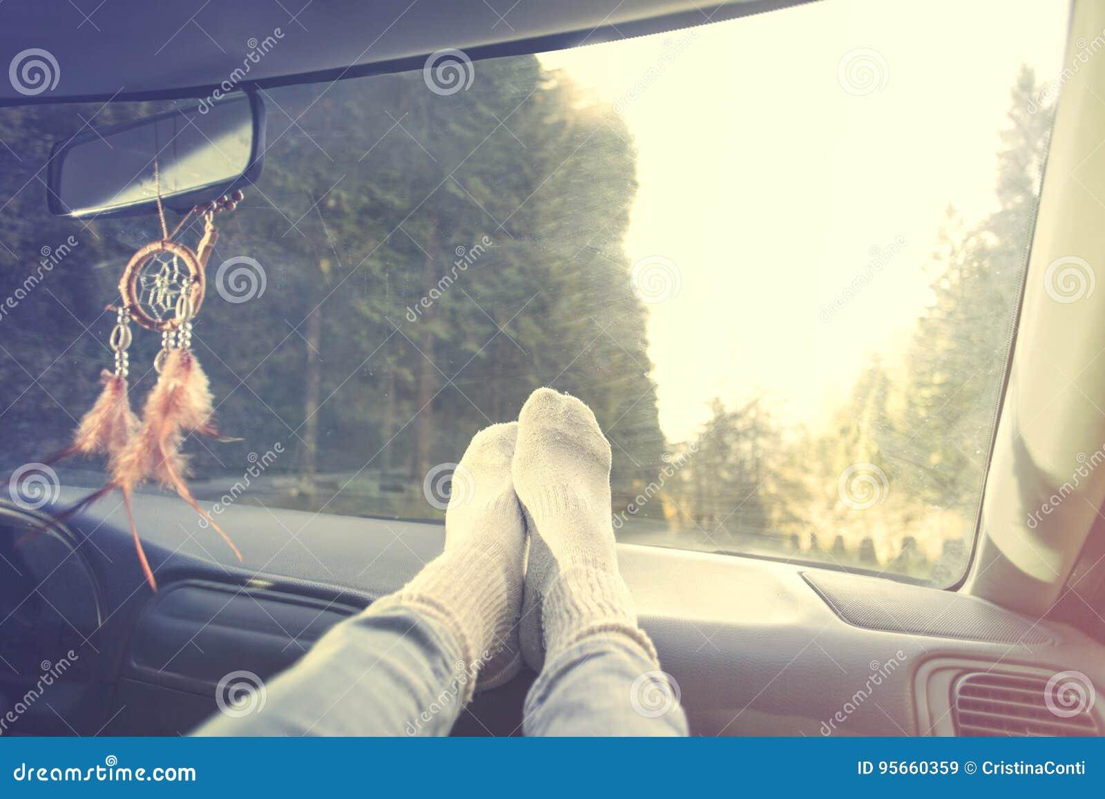 Расслабленная персона с ногами на приборной панели во время отключения автомобиля