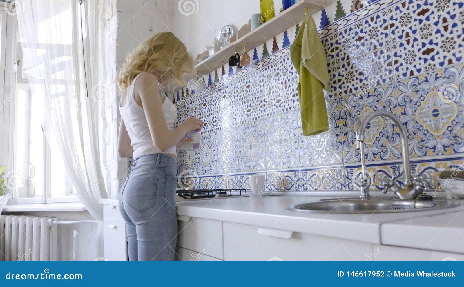 Расслабленная сексуальная блондинка представляя на кухне в утре E Сексуальная молодая белокурая женщина в кухне дома