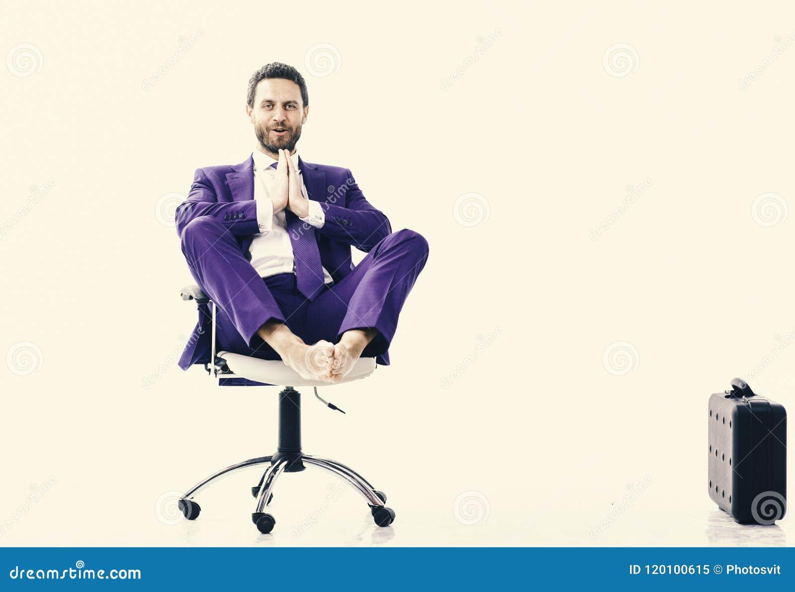 Расслабленный красивый кавказский молодой человек сидя и размышляя на стуле офиса, изолированном на белой предпосылке