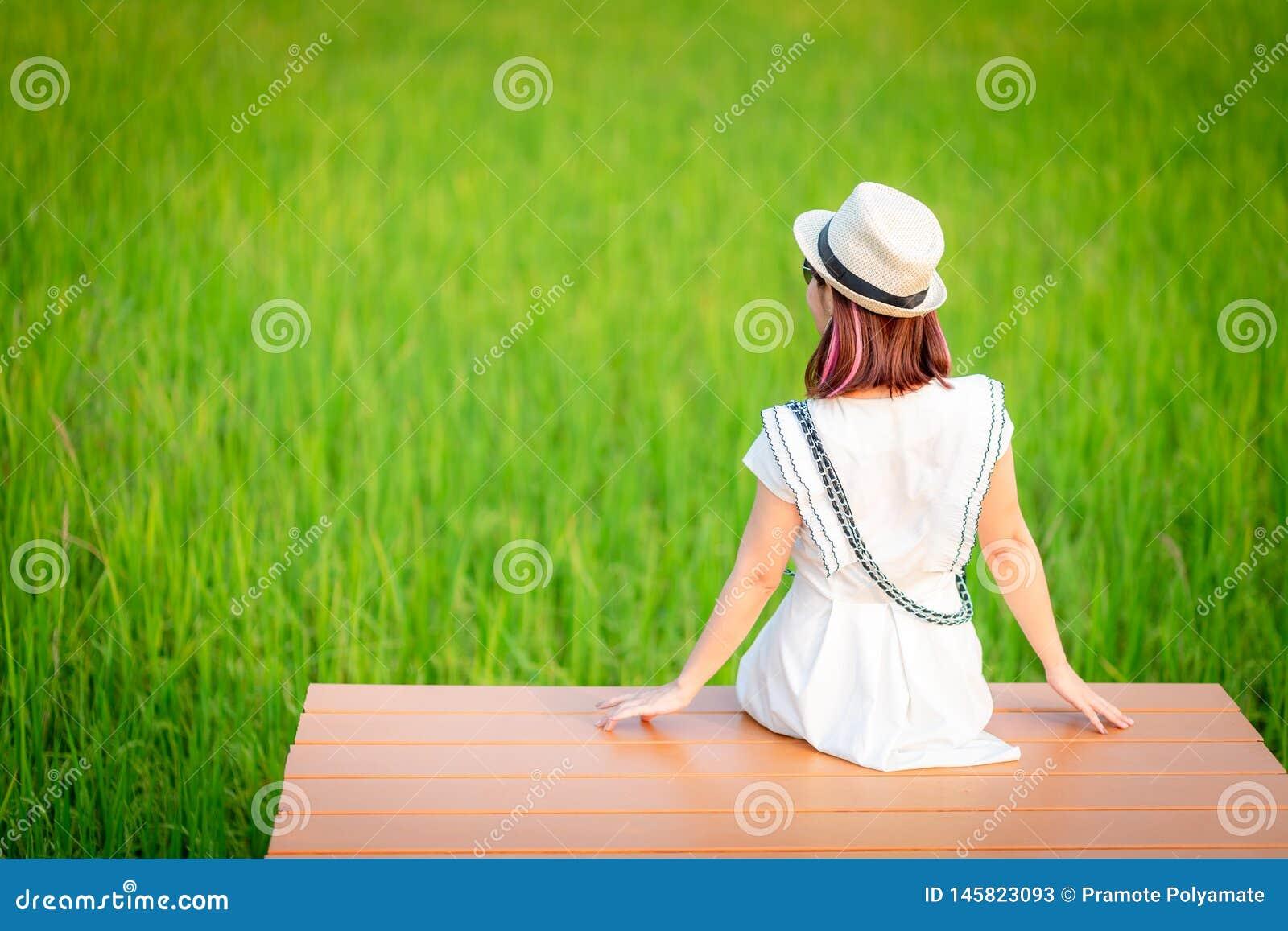 Расслабляющая молодая женщина сидя в природе на древесине, смотрящ зеленые поля, освежая природа, азиатская женщина сидя и