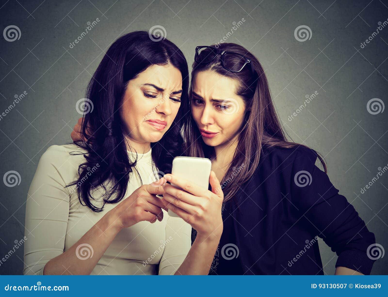 2 расстроенных женщины друзей осматривая на линии содержании на умном телефоне