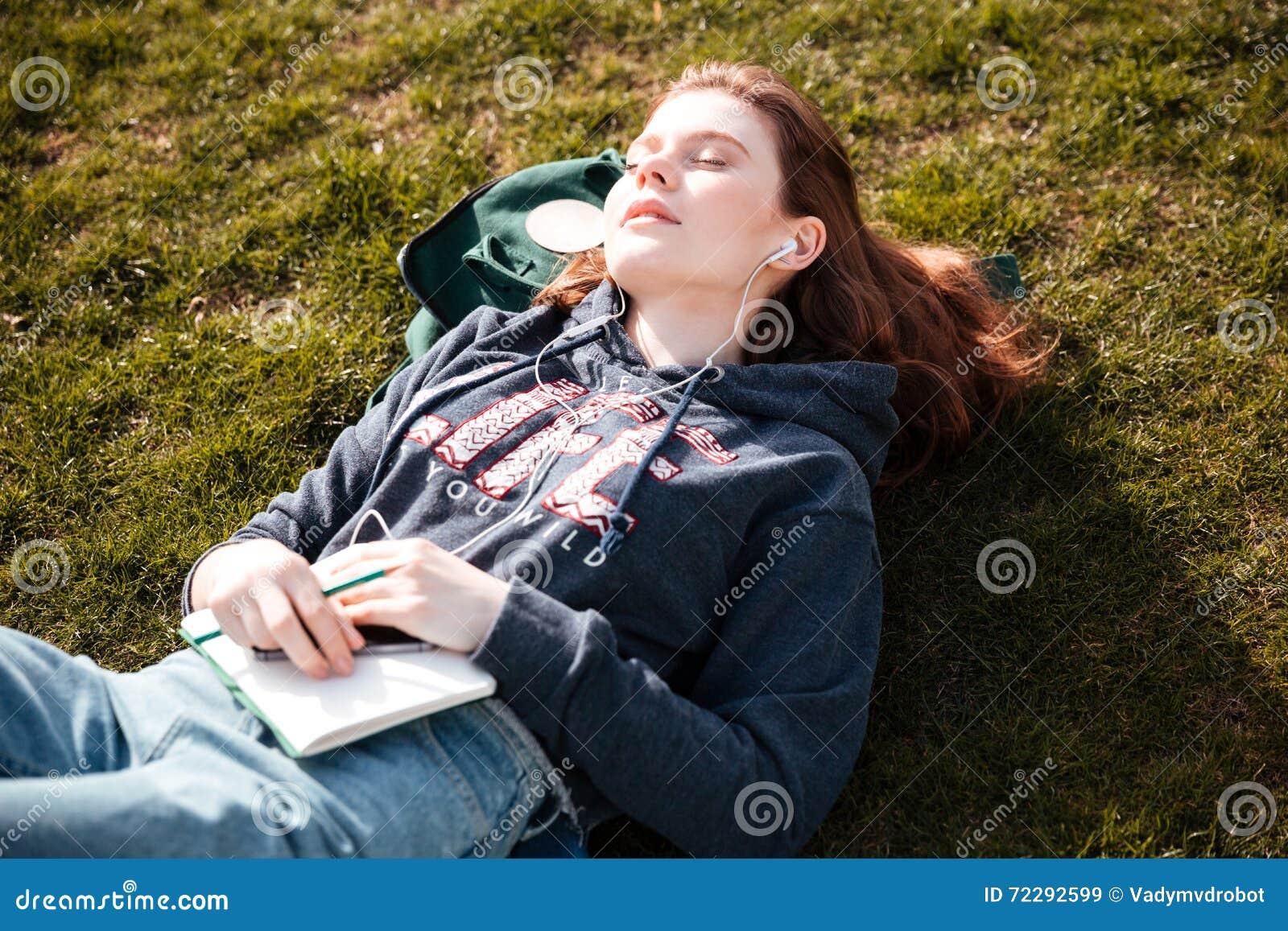 Download Расслабленная женщина лежа на лужайке и слушая к музыке Стоковое Изображение - изображение насчитывающей тетрадь, битник: 72292599