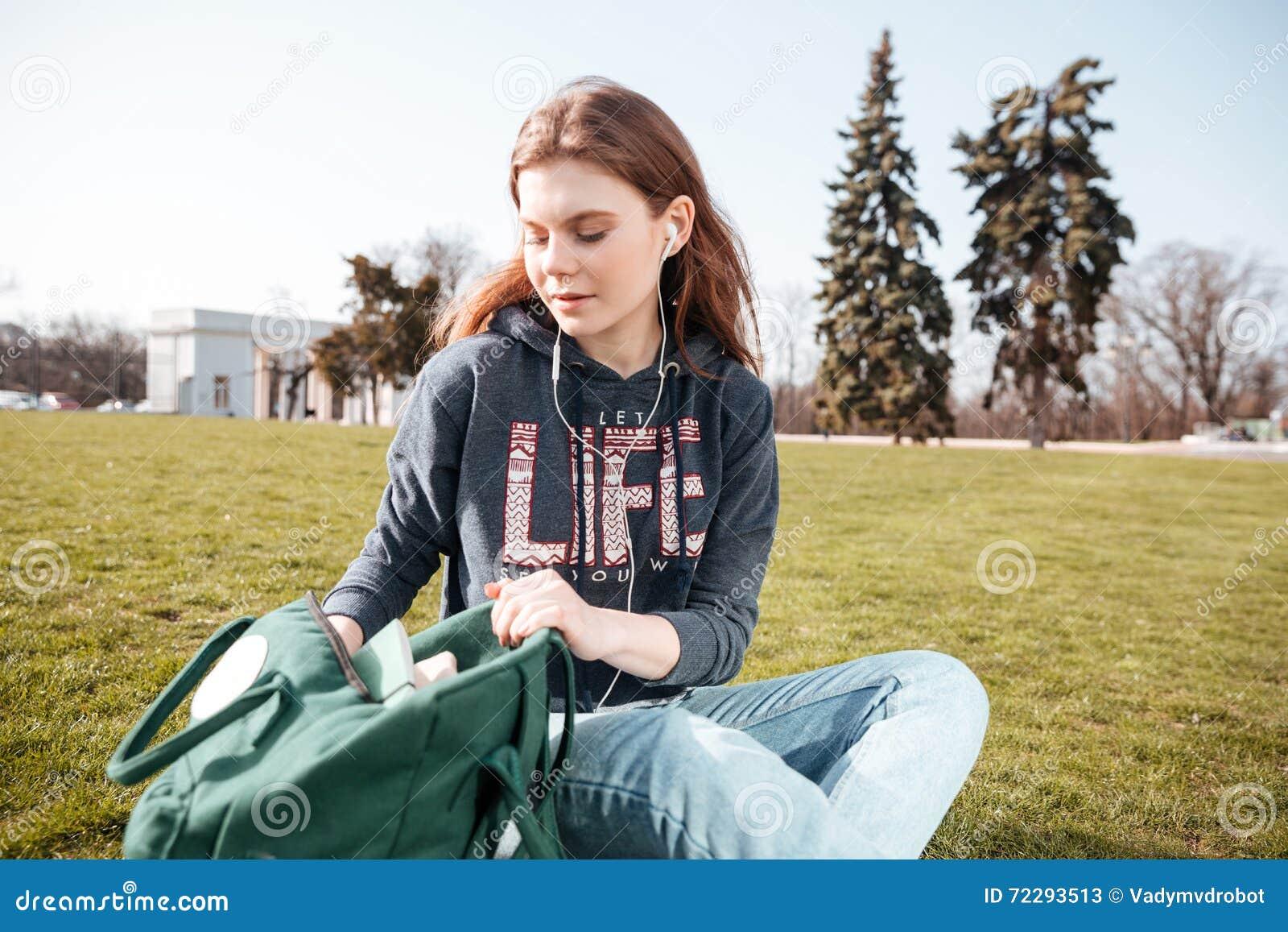 Download Расслабленная женщина сидя и слушая к музыке на траве Стоковое Изображение - изображение насчитывающей свобода, свободно: 72293513
