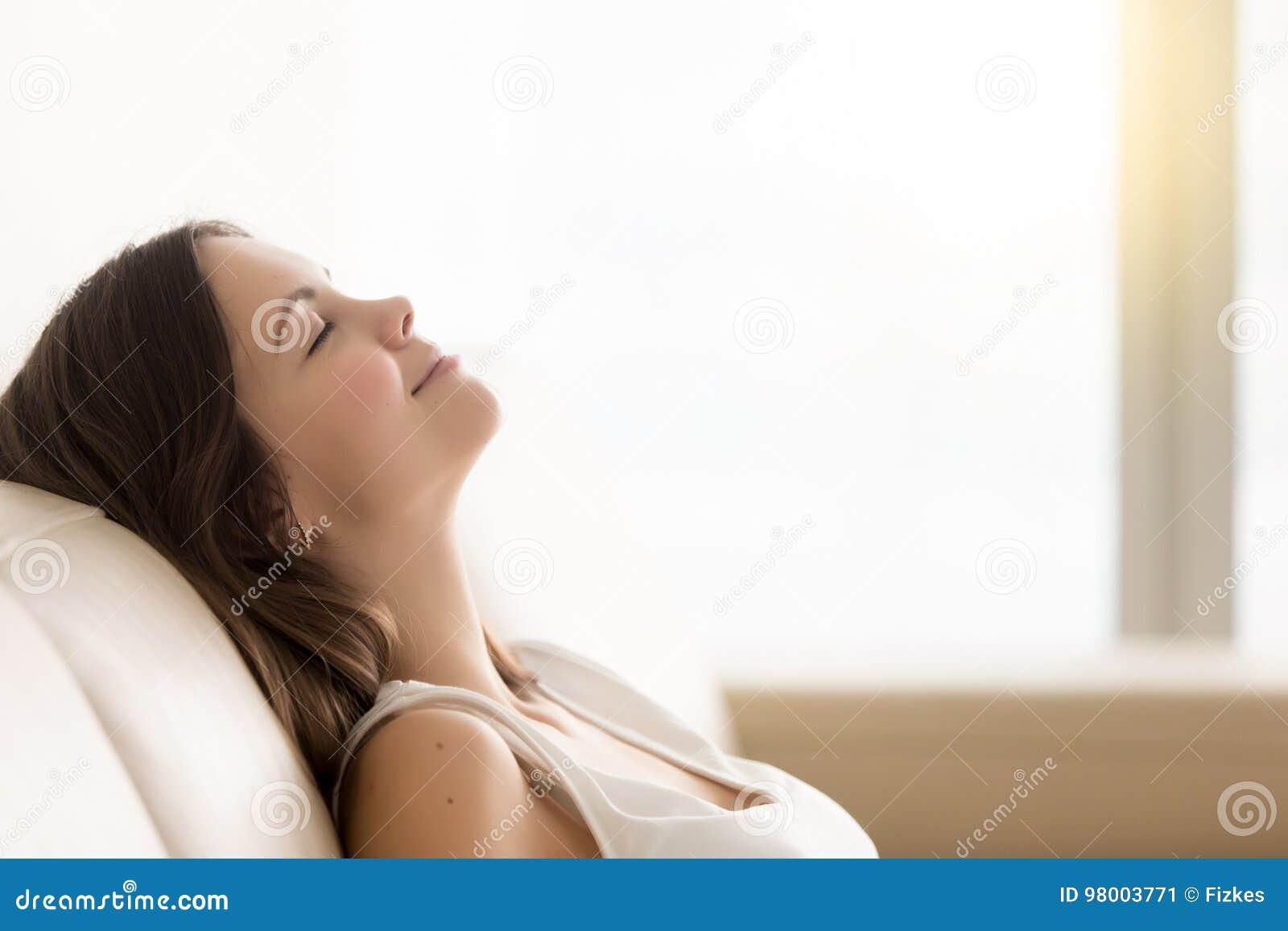 Расслабленная молодая женщина наслаждаясь остатками на удобной софе, spac экземпляра