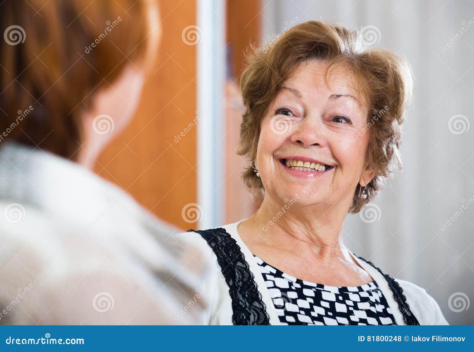 Расслабленные женские пенсионеры беседуя и усмехаясь крытые