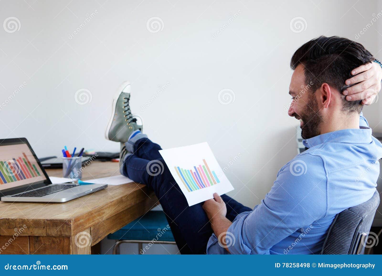 Расслабленные диаграммы дела чтения человека на офисе