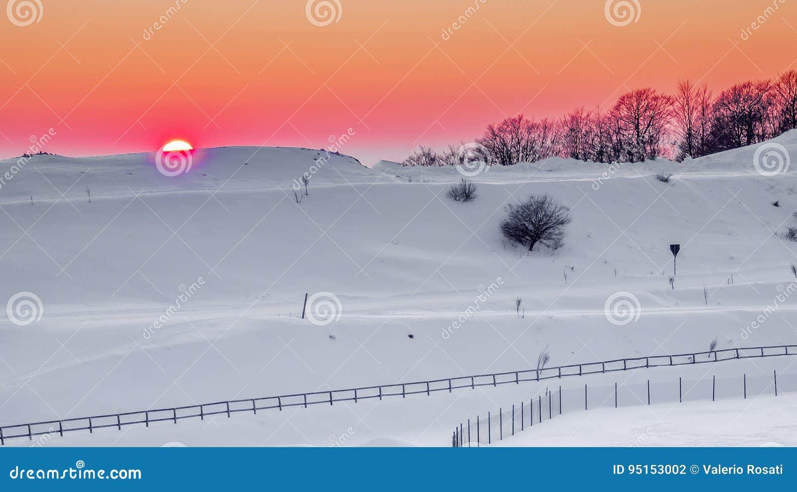 Расслабляющий теплый заход солнца в снежном ландшафте