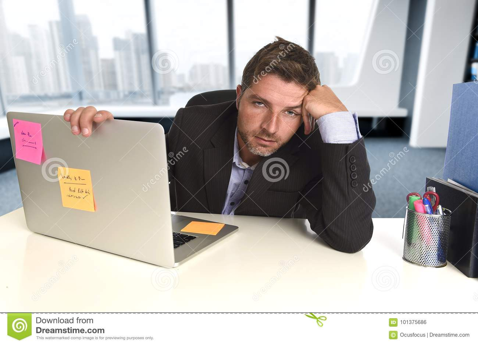 Расточительствованный бизнесмен работая в стрессе на портативном компьютере офиса смотря вымотанный