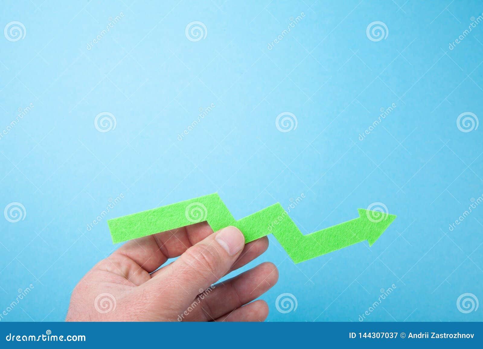 Растя зеленая стрелка вверх в руке, пустом космосе для текста