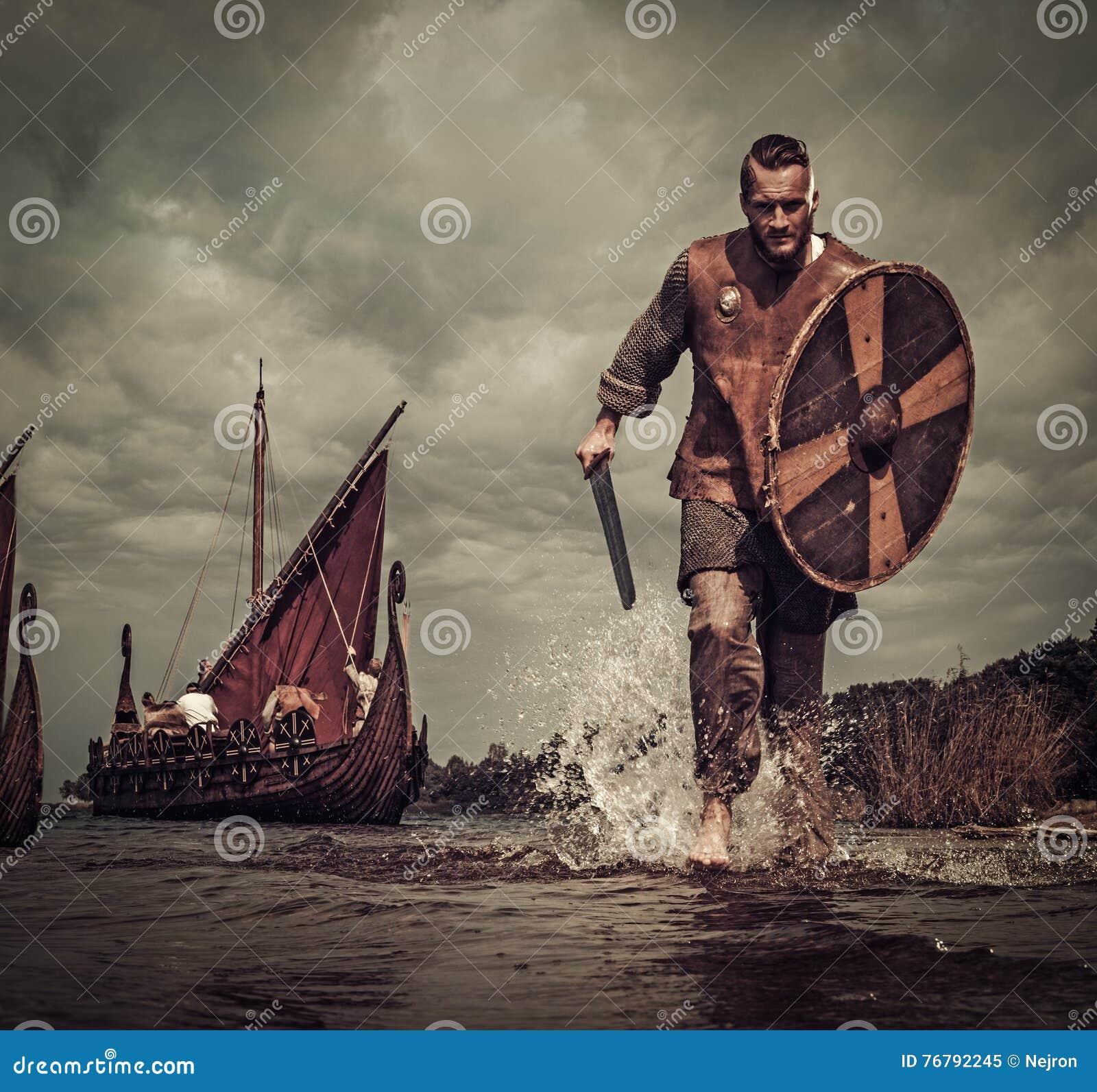 Ратник Викинга в нападении, бежать вдоль берега с Drakkar на предпосылке