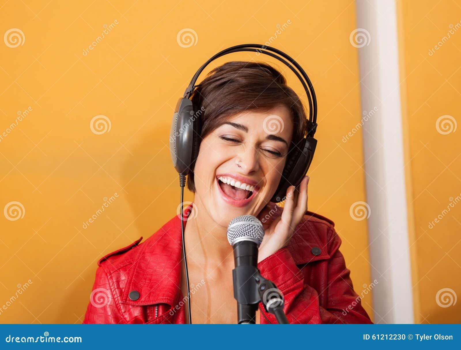 Радостная женщина поя в студии звукозаписи