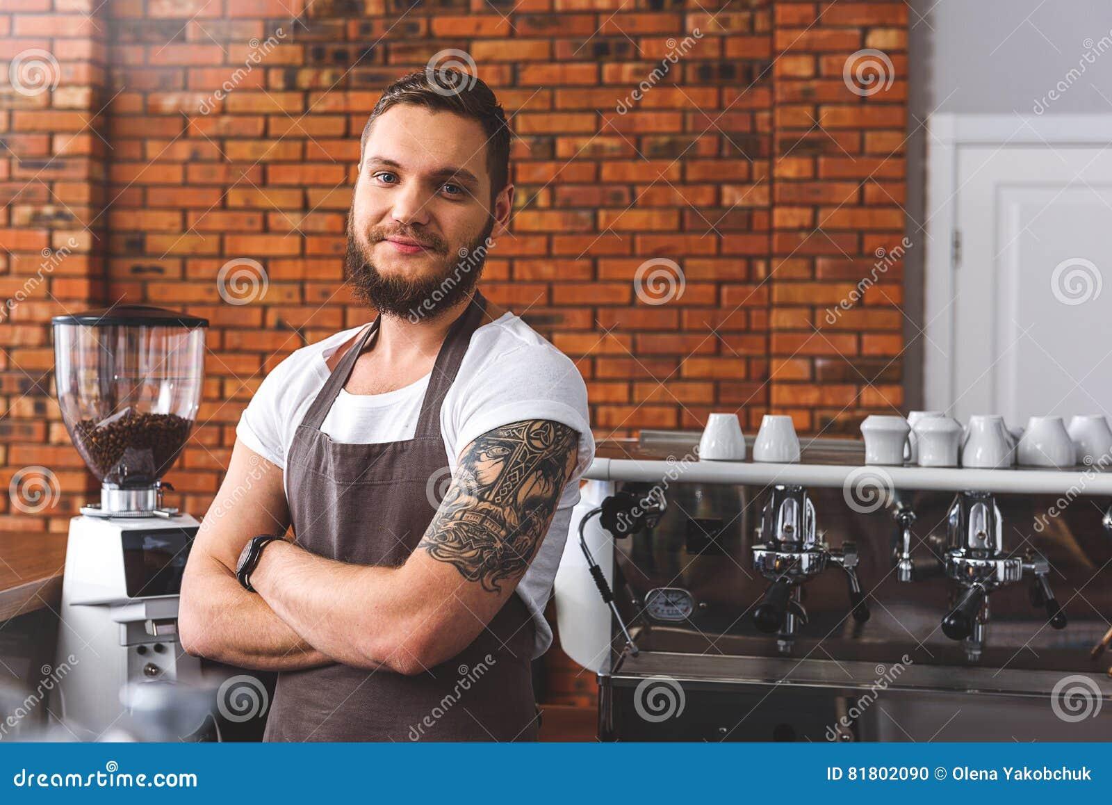 Радостный бородатый бармен работая в кофейне