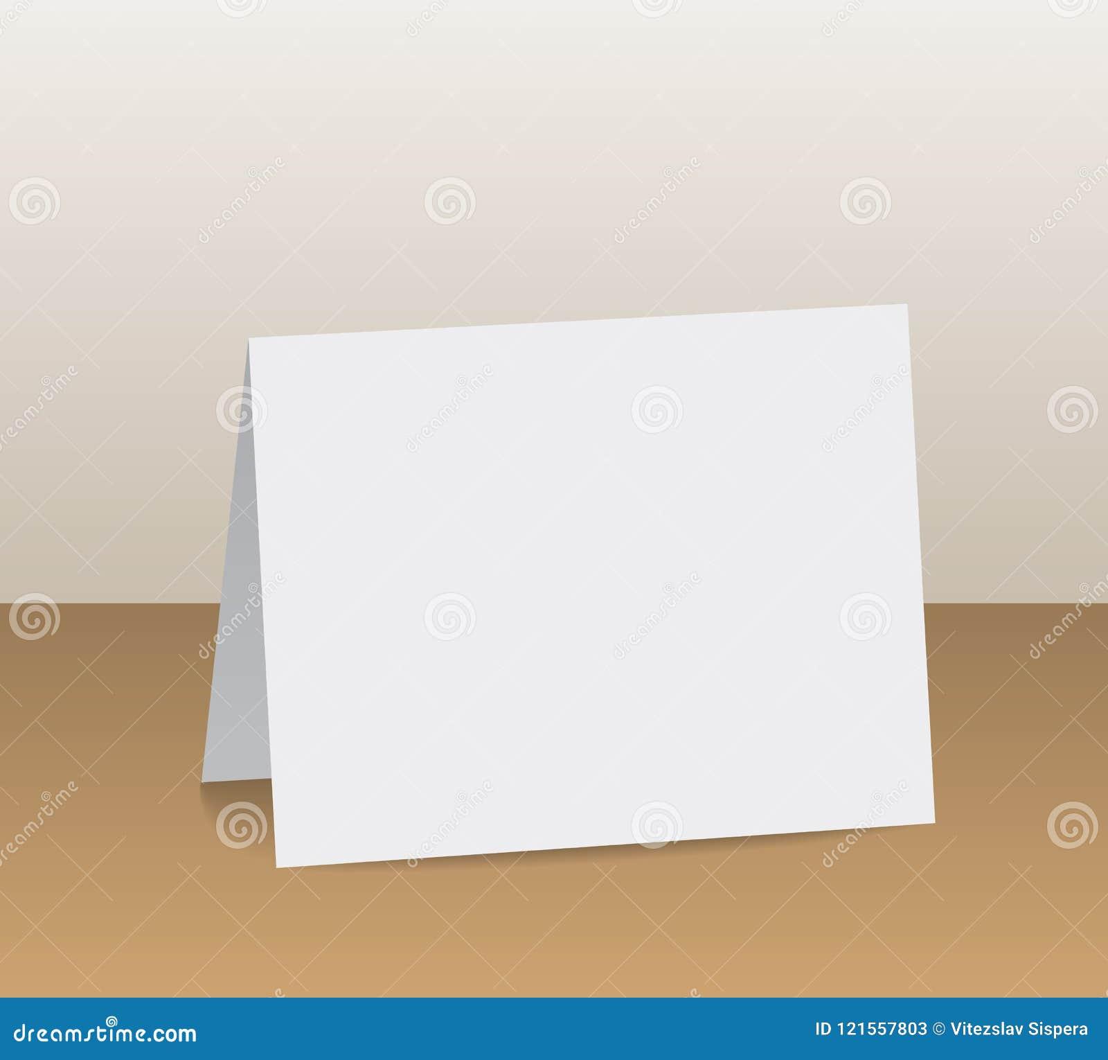 Реалистический белый пробел сложил бумажную карточку стоя на деревянном столе