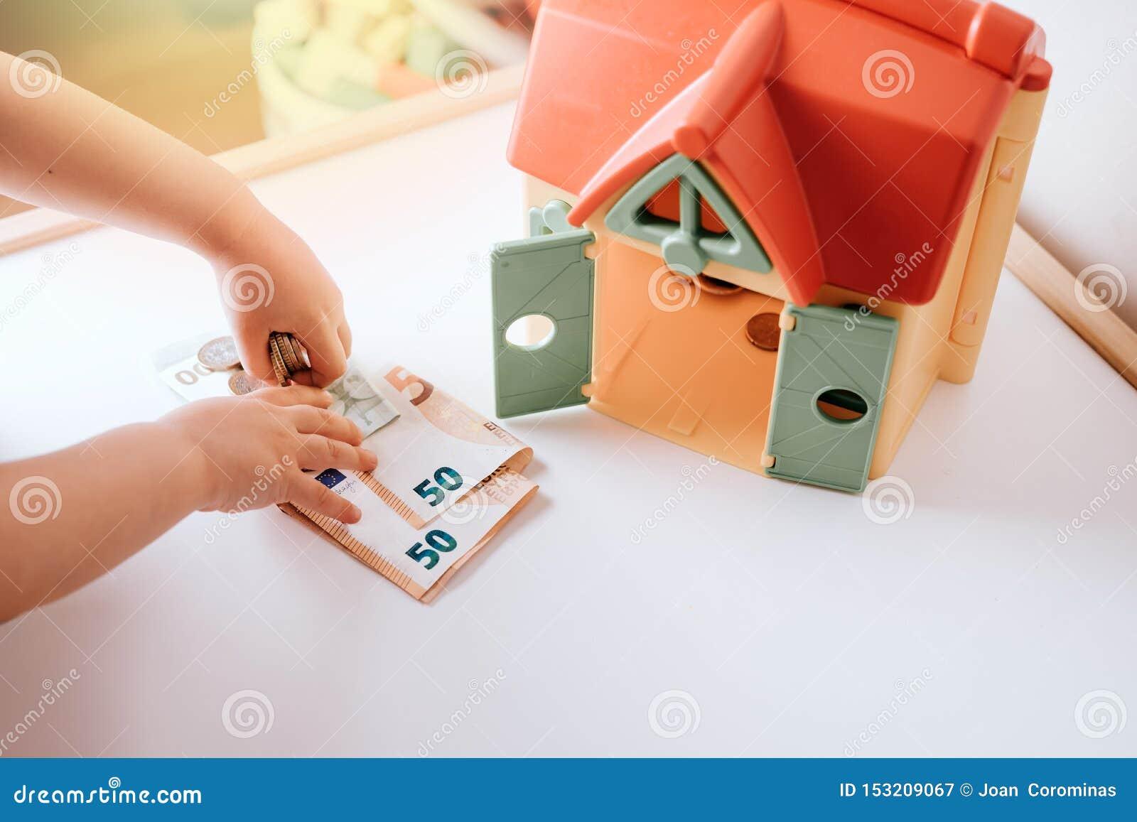 ребенк девушки, монетка вставки к сейфу, сохраняя концепции денег над белым фото запаса предпосылки