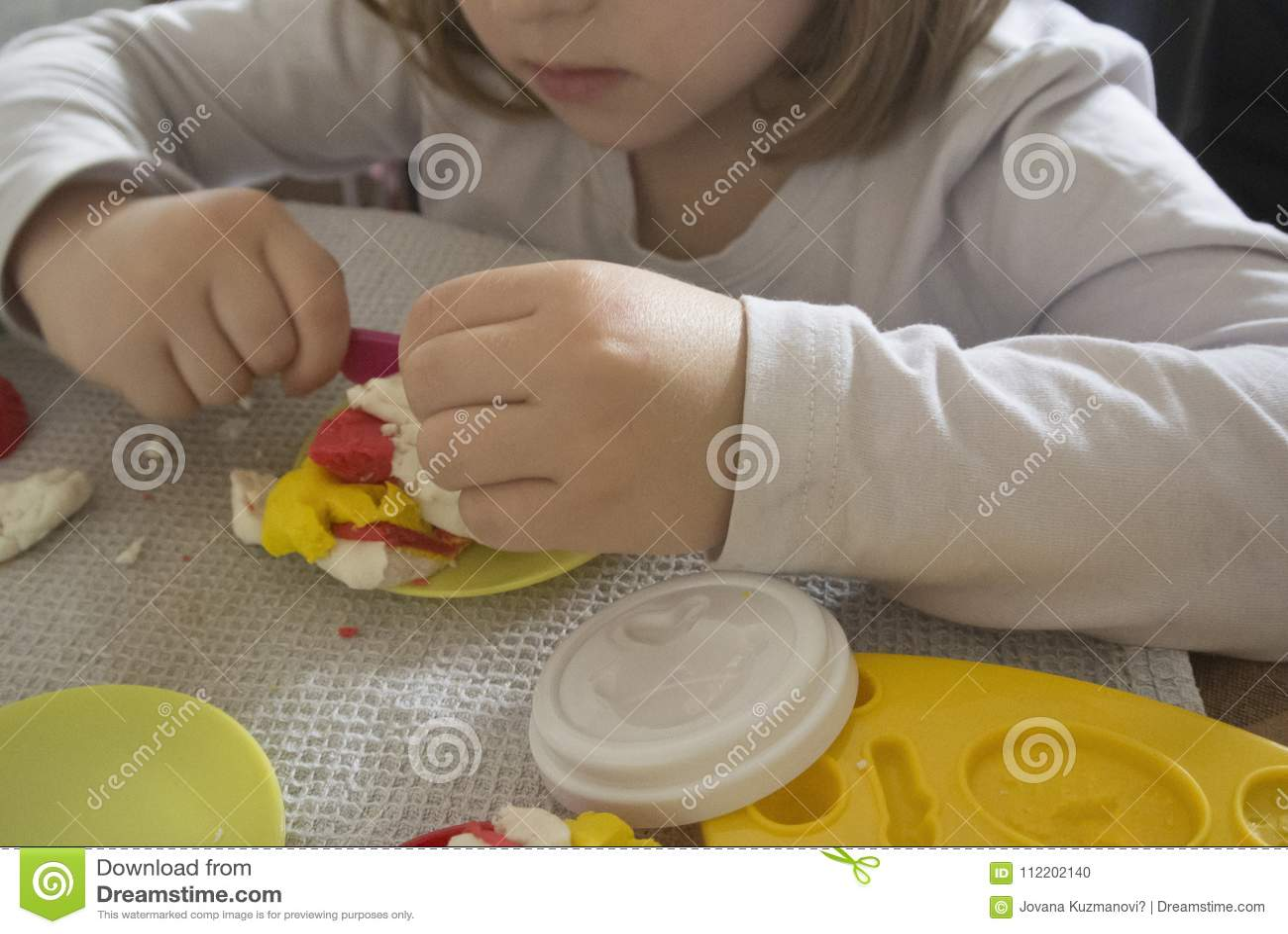 Ребенк играя с пластилином