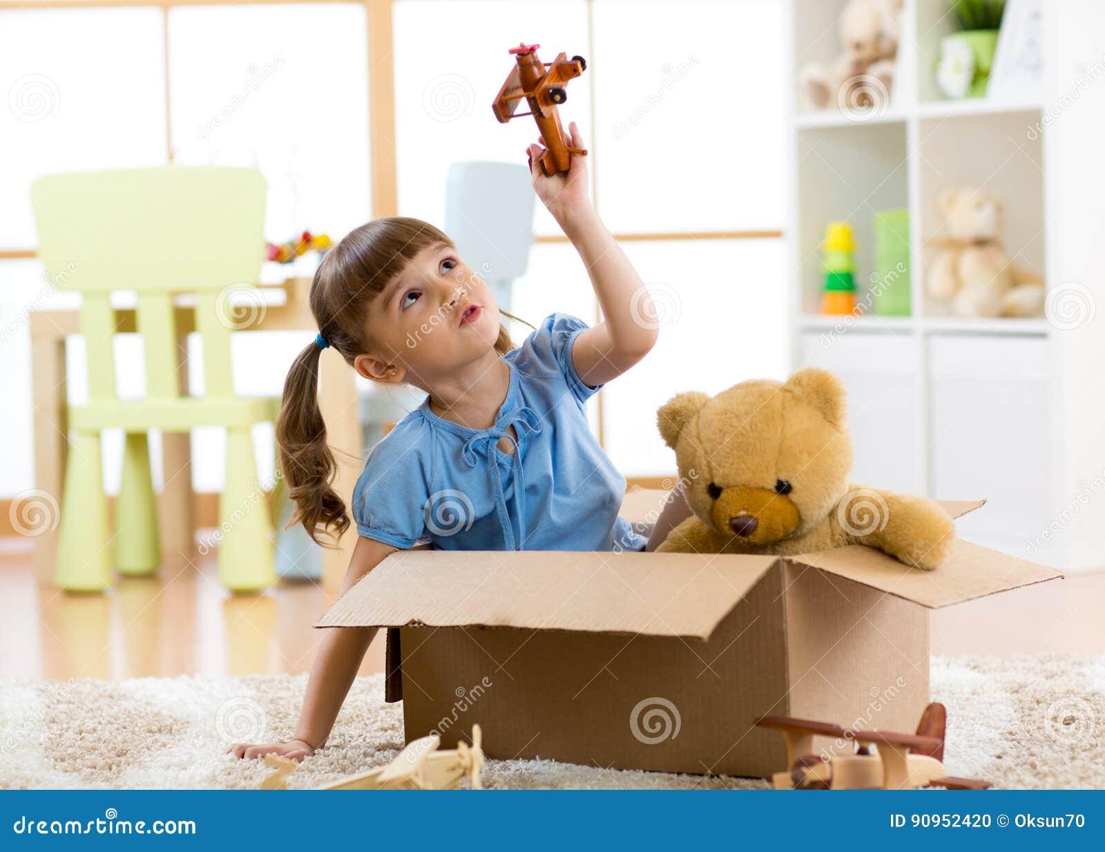 Ребенк играя с плоской игрушкой дома Концепция перемещения, свободы и воображения