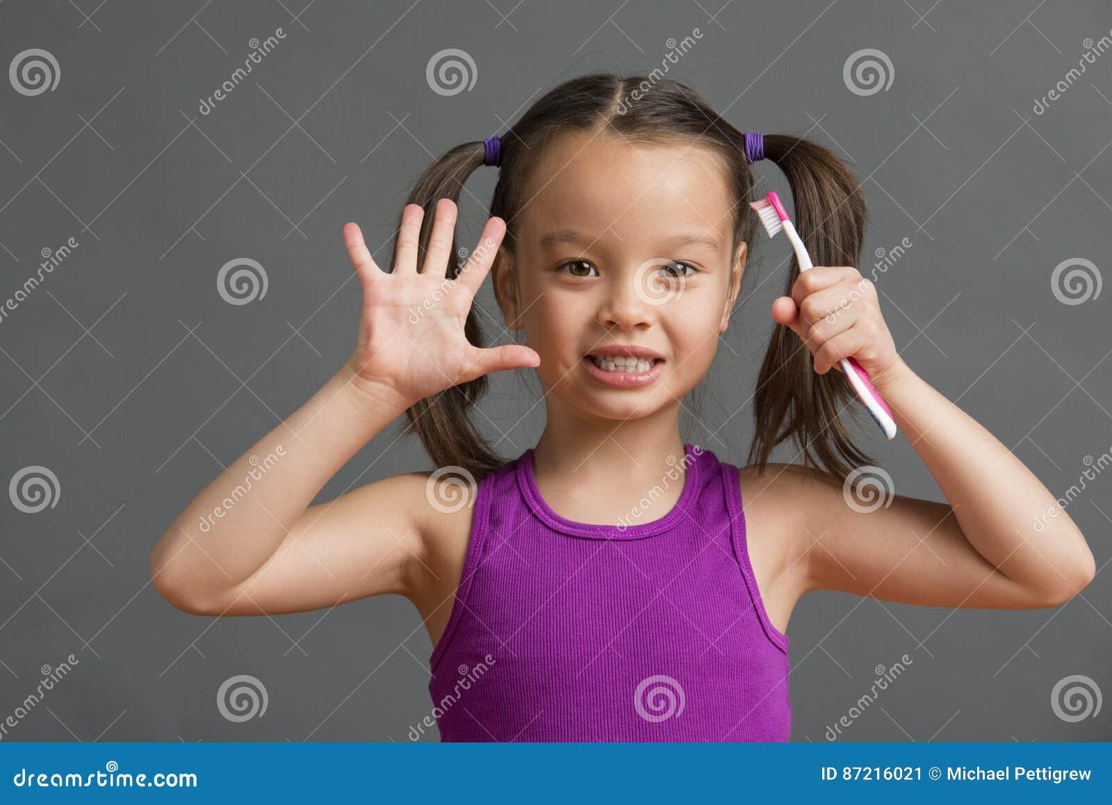 Ребенк показывая 5 пока держащ зубную щетку