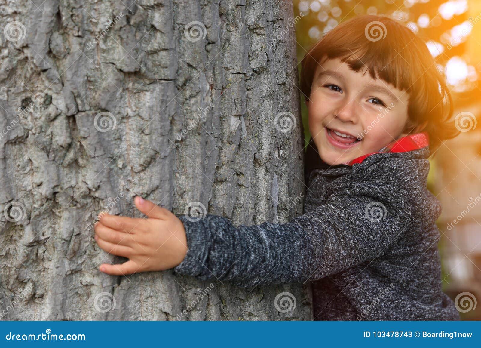 Ребенк ребенка обнимая природу охраны окружающей среды дерева внешнюю