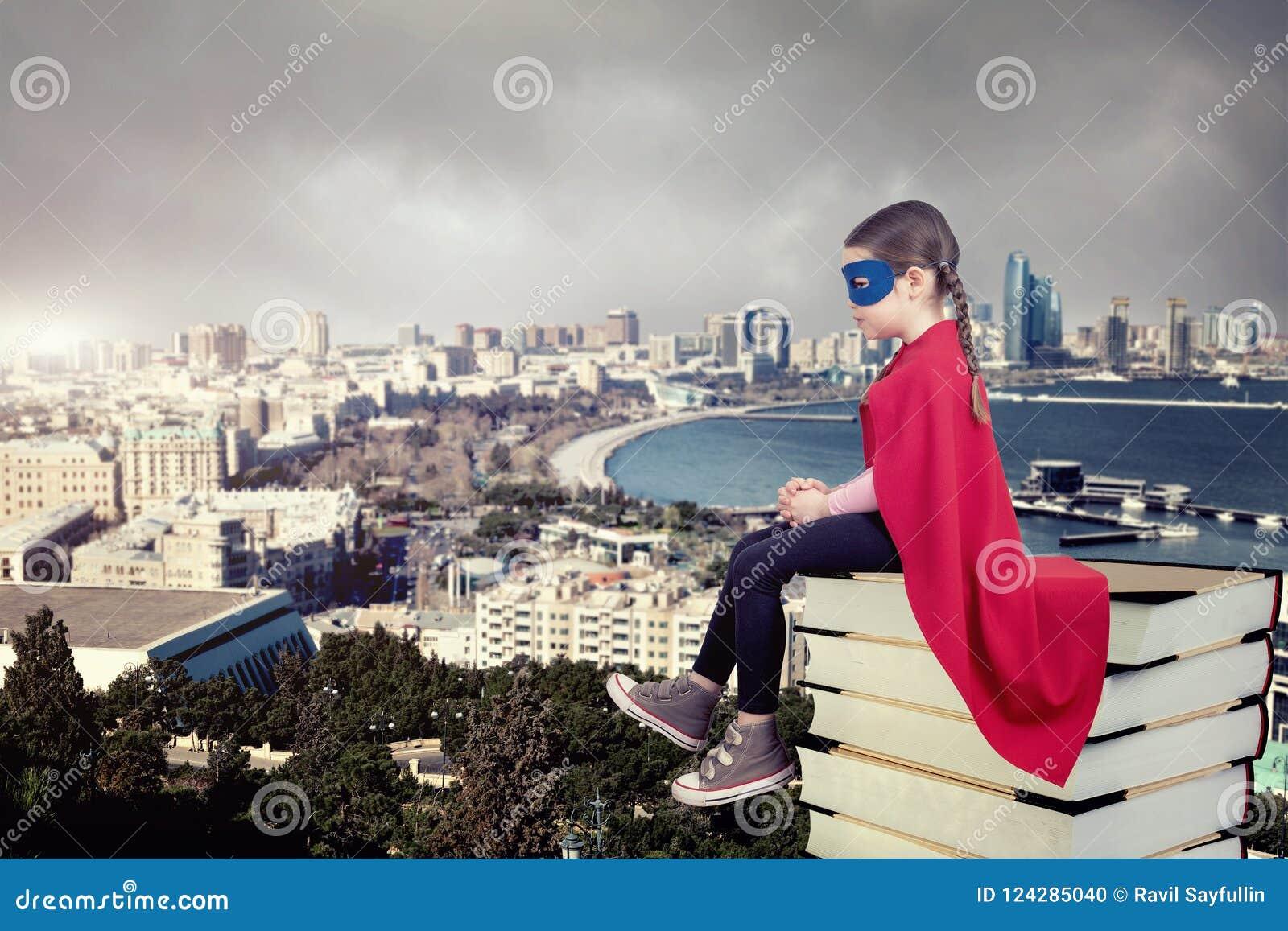 Ребенк супергероя сидя на стоге книг против городской предпосылки
