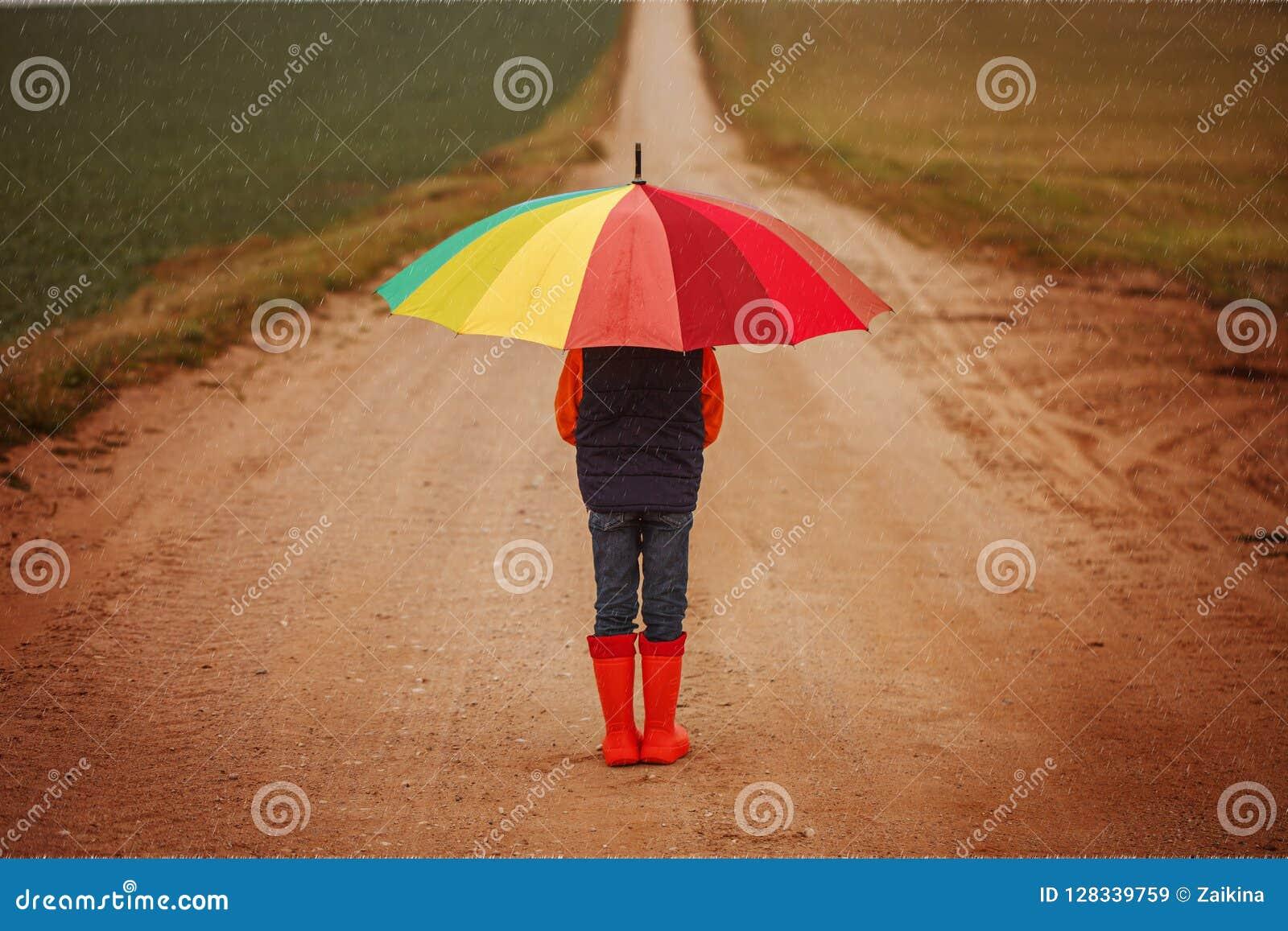 Ребенок в оранжевых резиновых ботинках держа красочный зонтик под дождем в осени задний взгляд