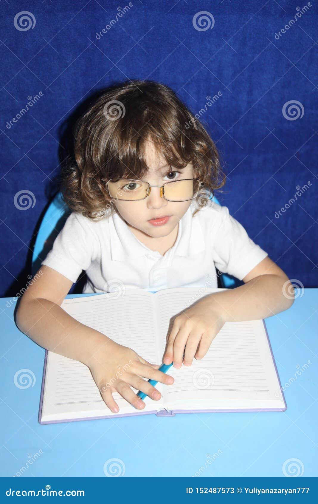 Ребенок делает уроки с серьезным взглядом в стеклах