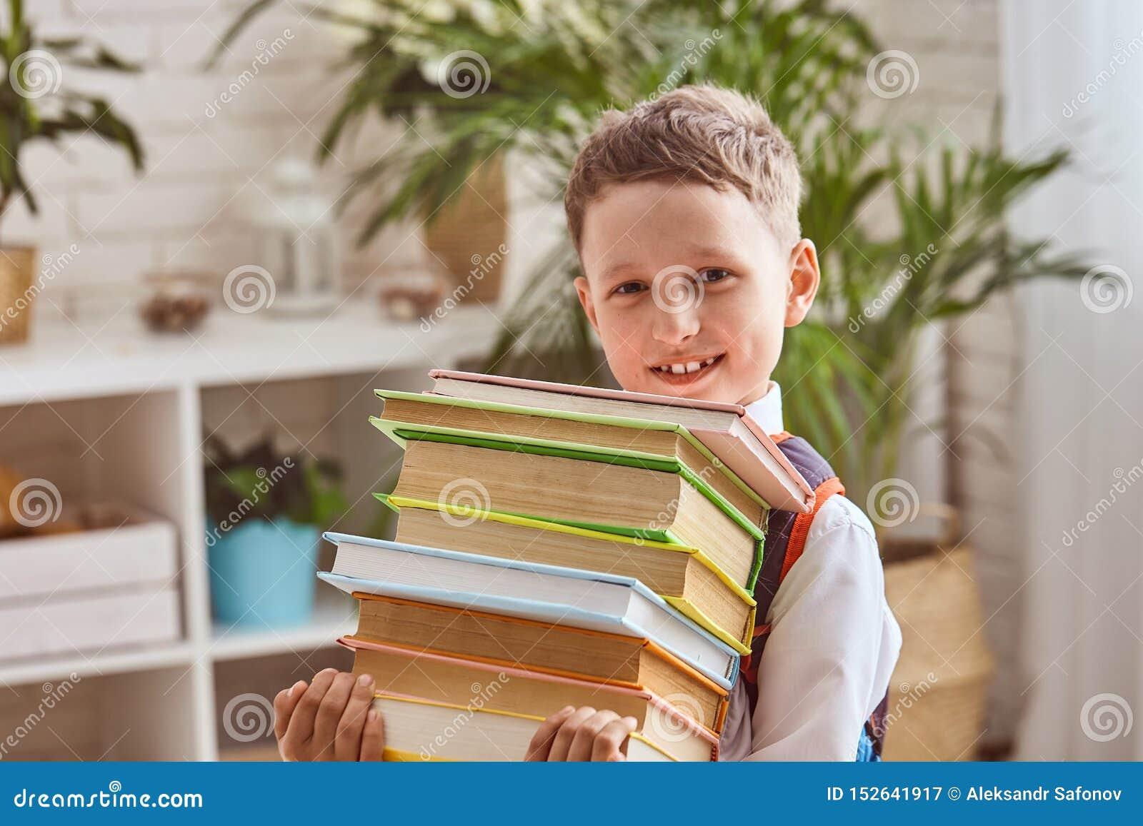 Ребенок держит стог учебников