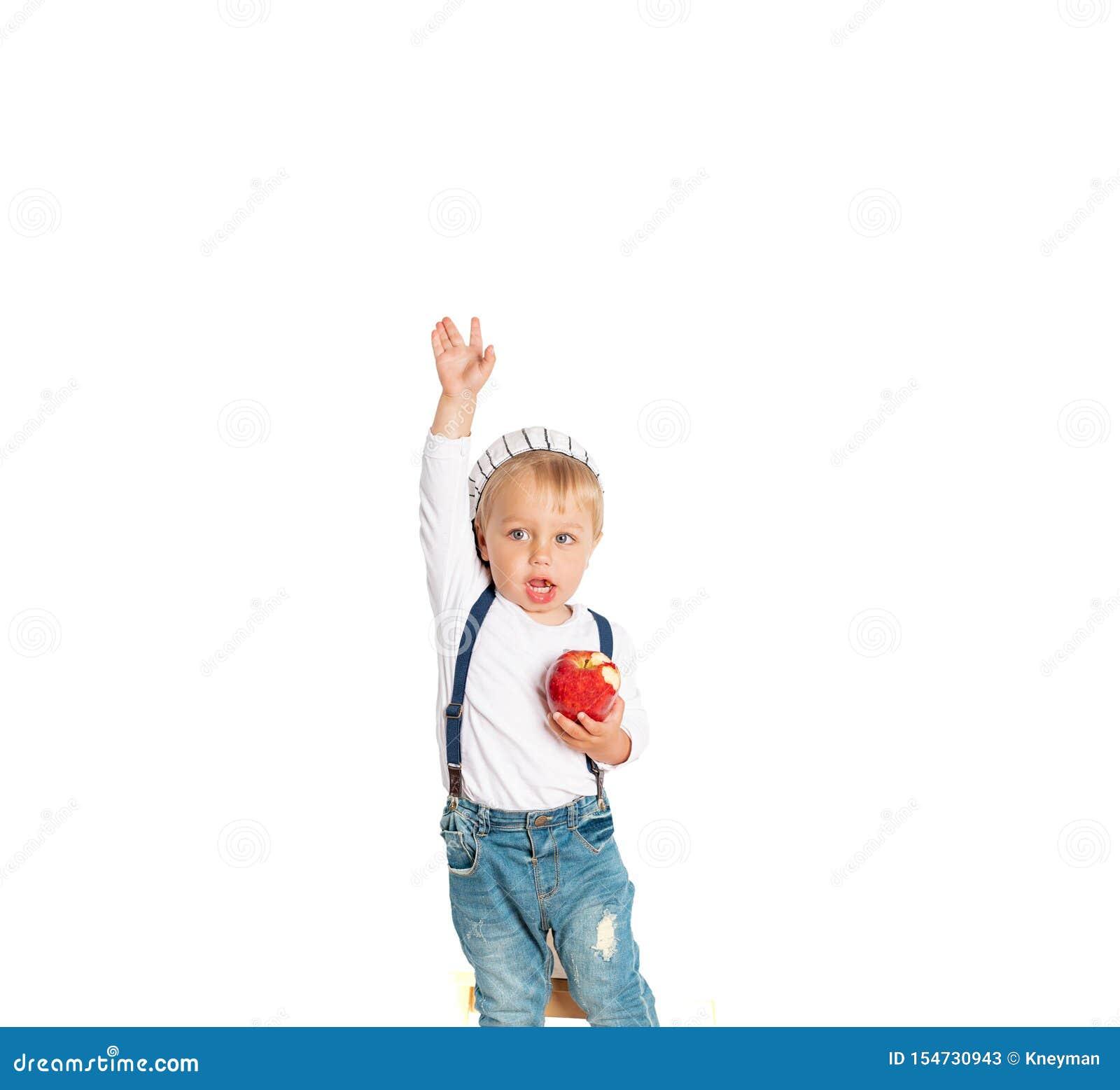 Ребенок есть яблоко и усмехаясь в студии изолированной на белой предпосылке