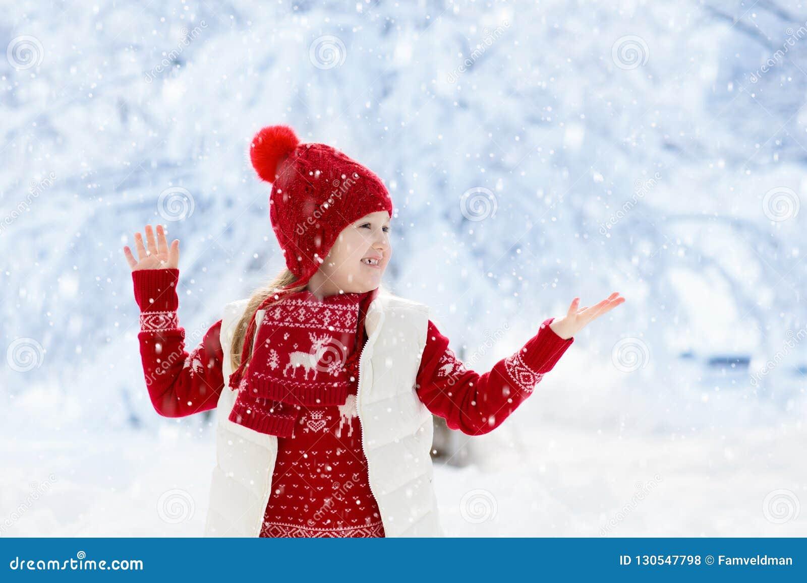 Ребенок играя в снеге на рождестве Малыши в зиме