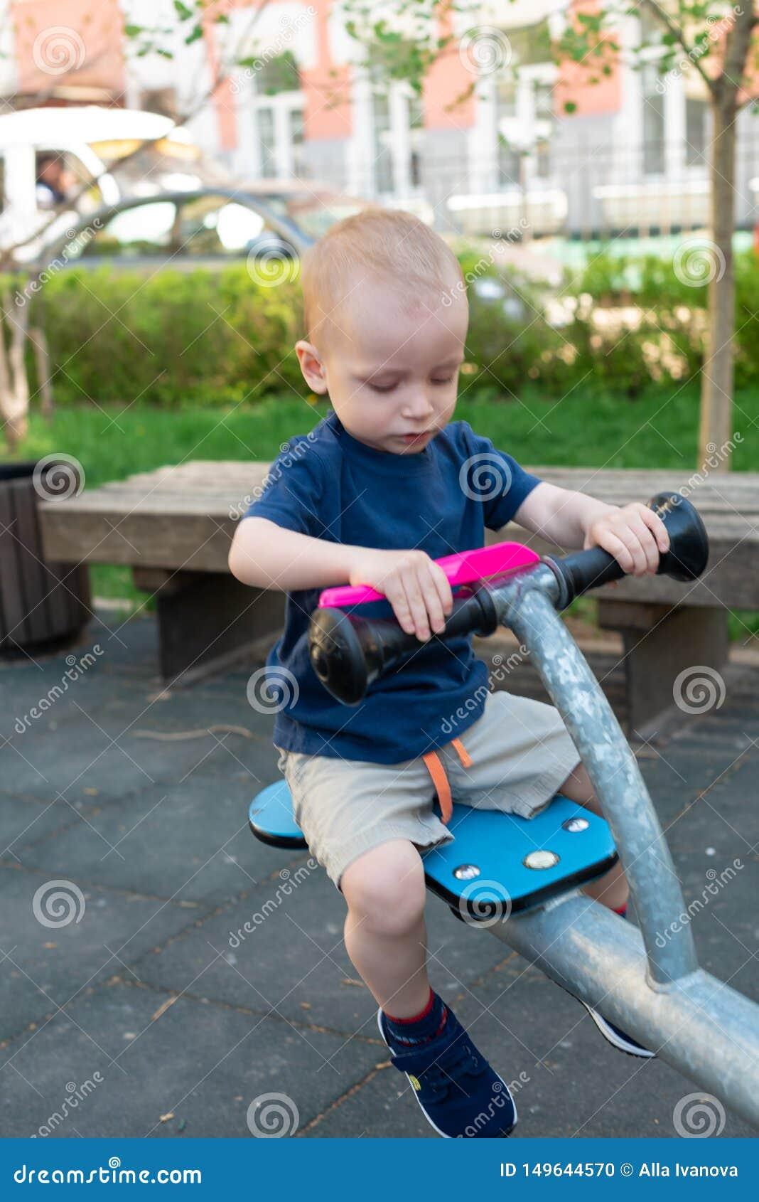 Ребенок играя на на открытом воздухе спортивной площадке летом Дети играют на дворе детского сада Активный ребенк держа качание и