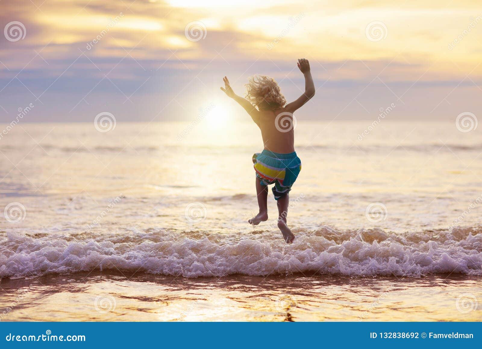Ребенок играя на пляже океана Ребенк на море захода солнца