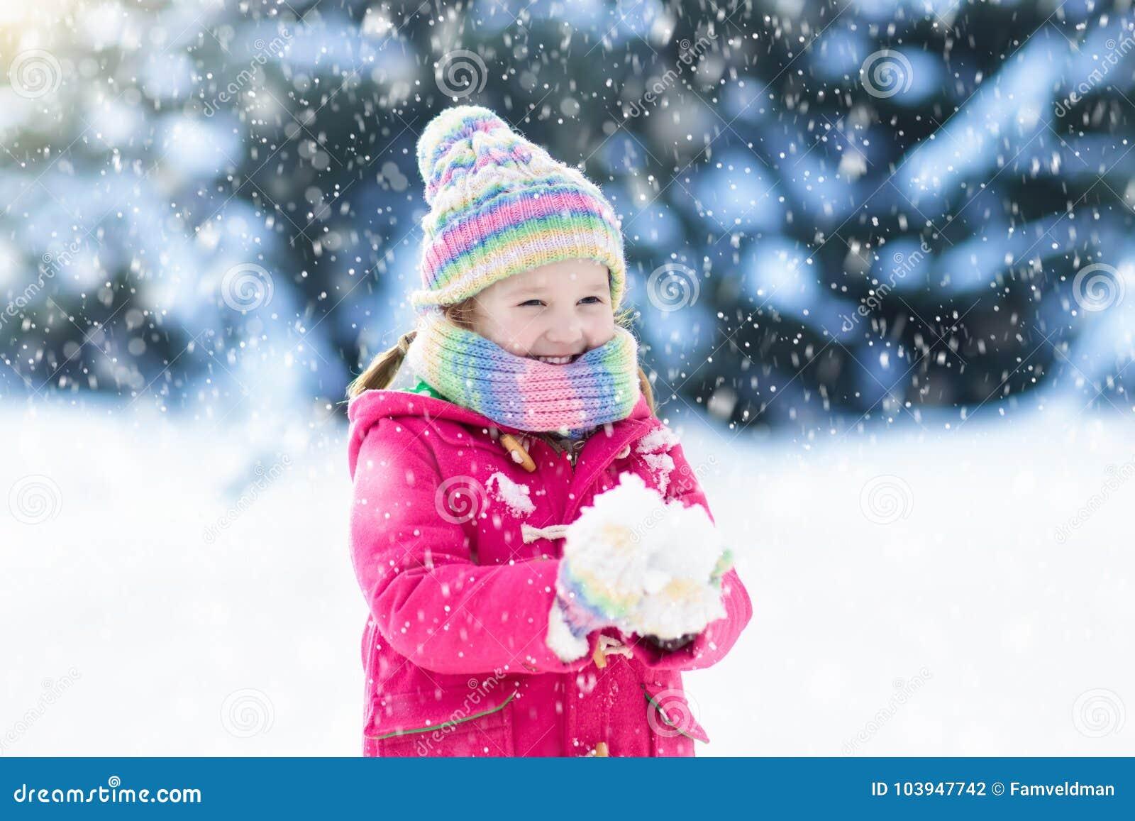 Ребенок играя с снегом в зиме малыши outdoors