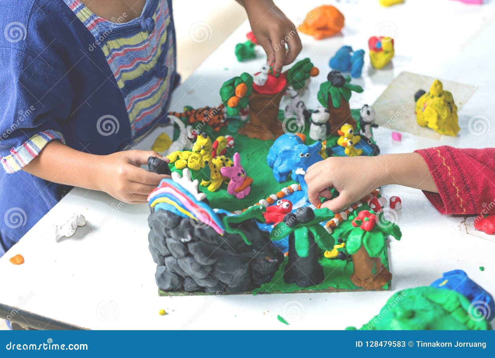 Ребенок играя с формами прессформы глины, творческие способности детей