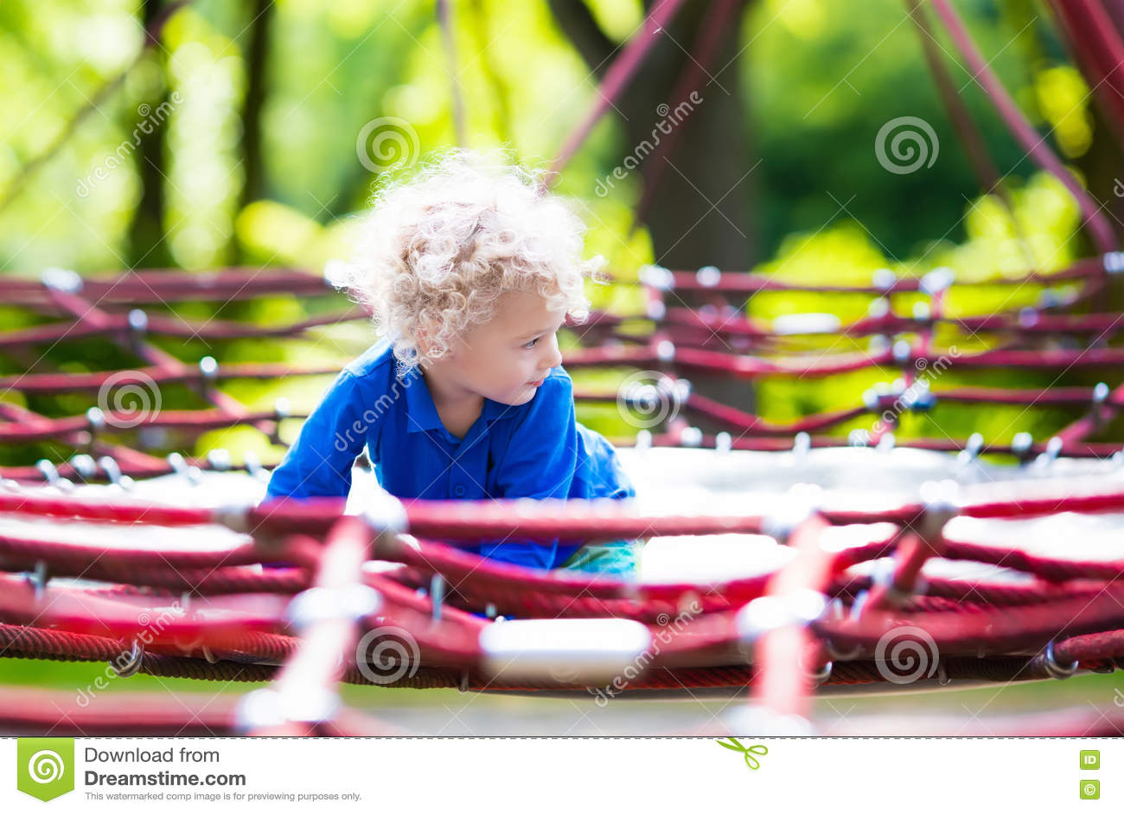 Ребенок имея потеху на спортивной площадке школьного двора