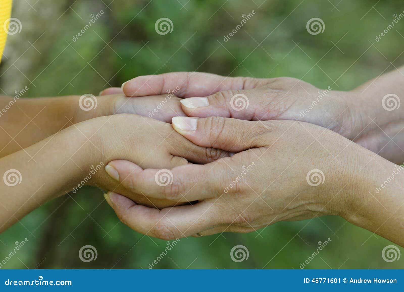 Ребенок и мать держа руки