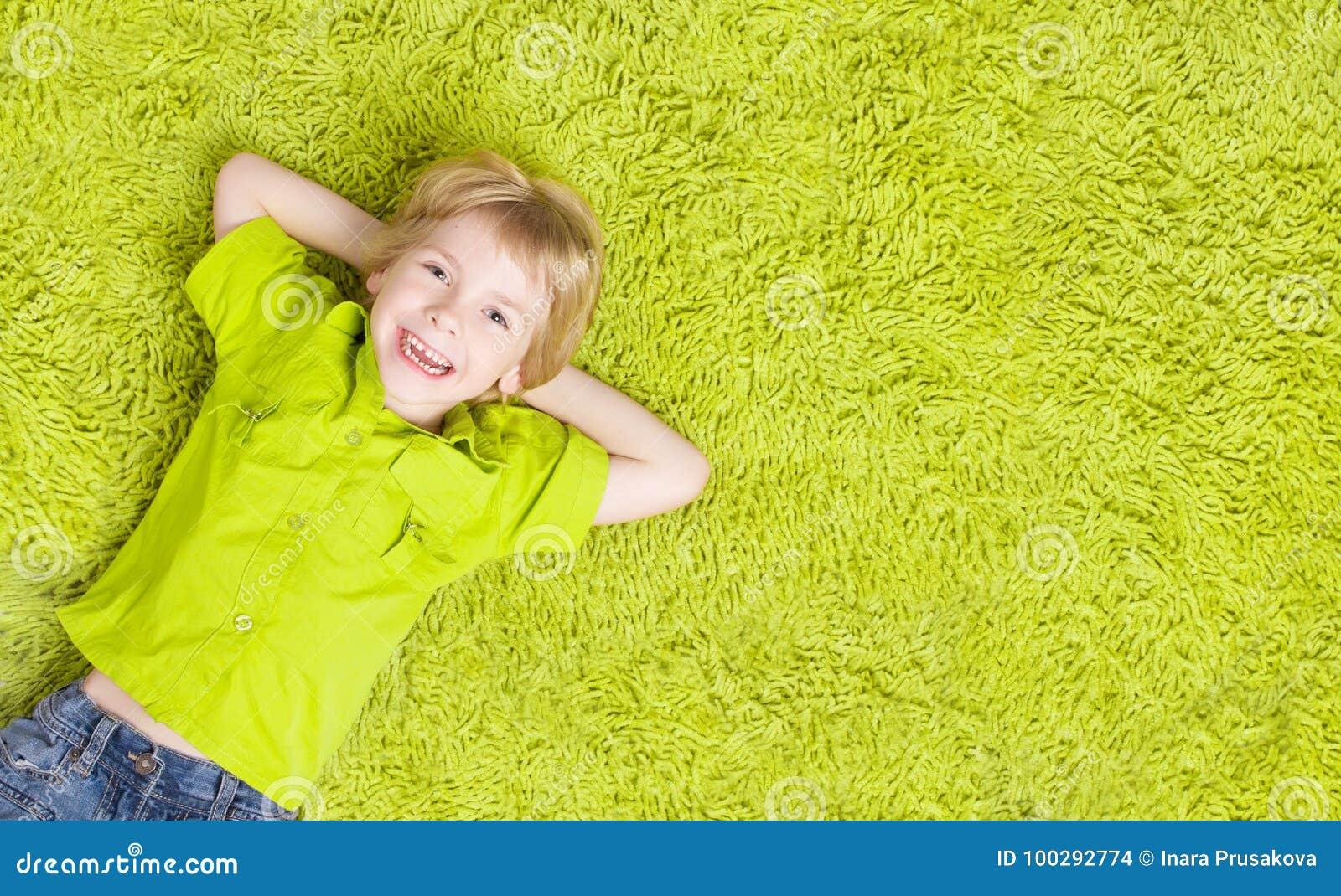 Ребенок лежа над зеленым ковром Счастливый усмехаясь мальчик ребенк