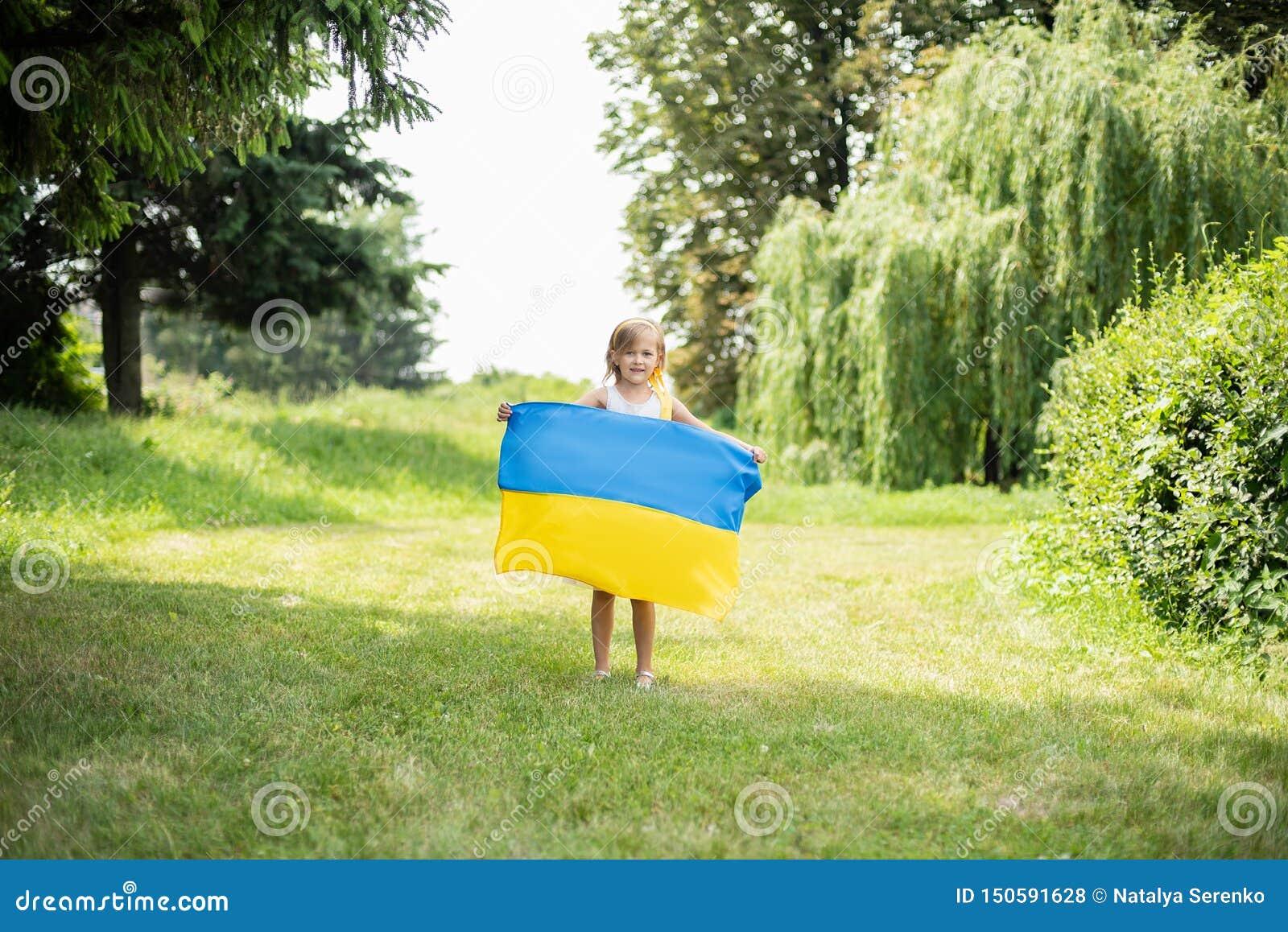 Ребенок носит порхать голубой и желтый флаг Украины в поле День независимости Украины День флага День Конституции Девушка i