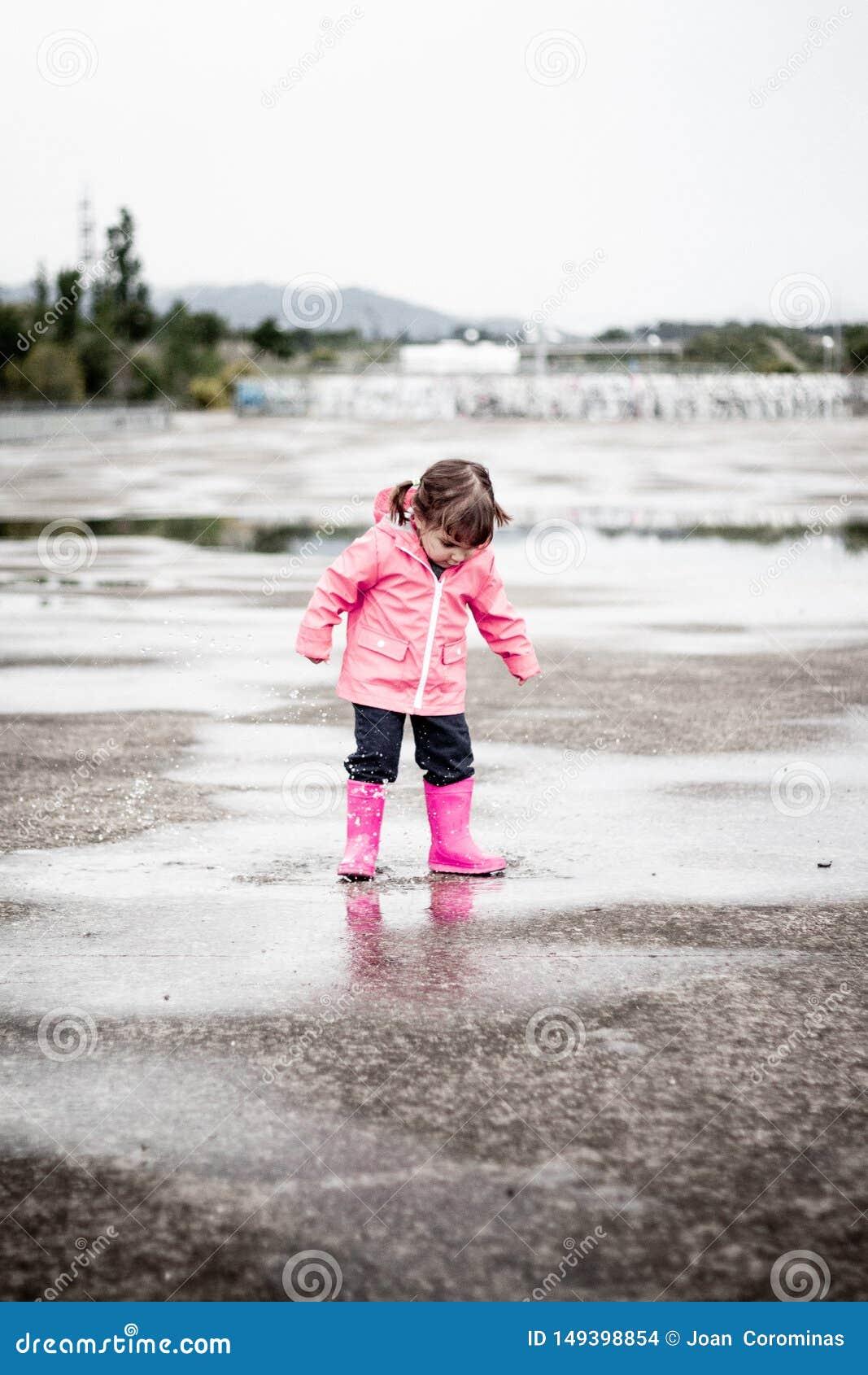 Ребенок одетый в розовых одеждах скача в лужицы