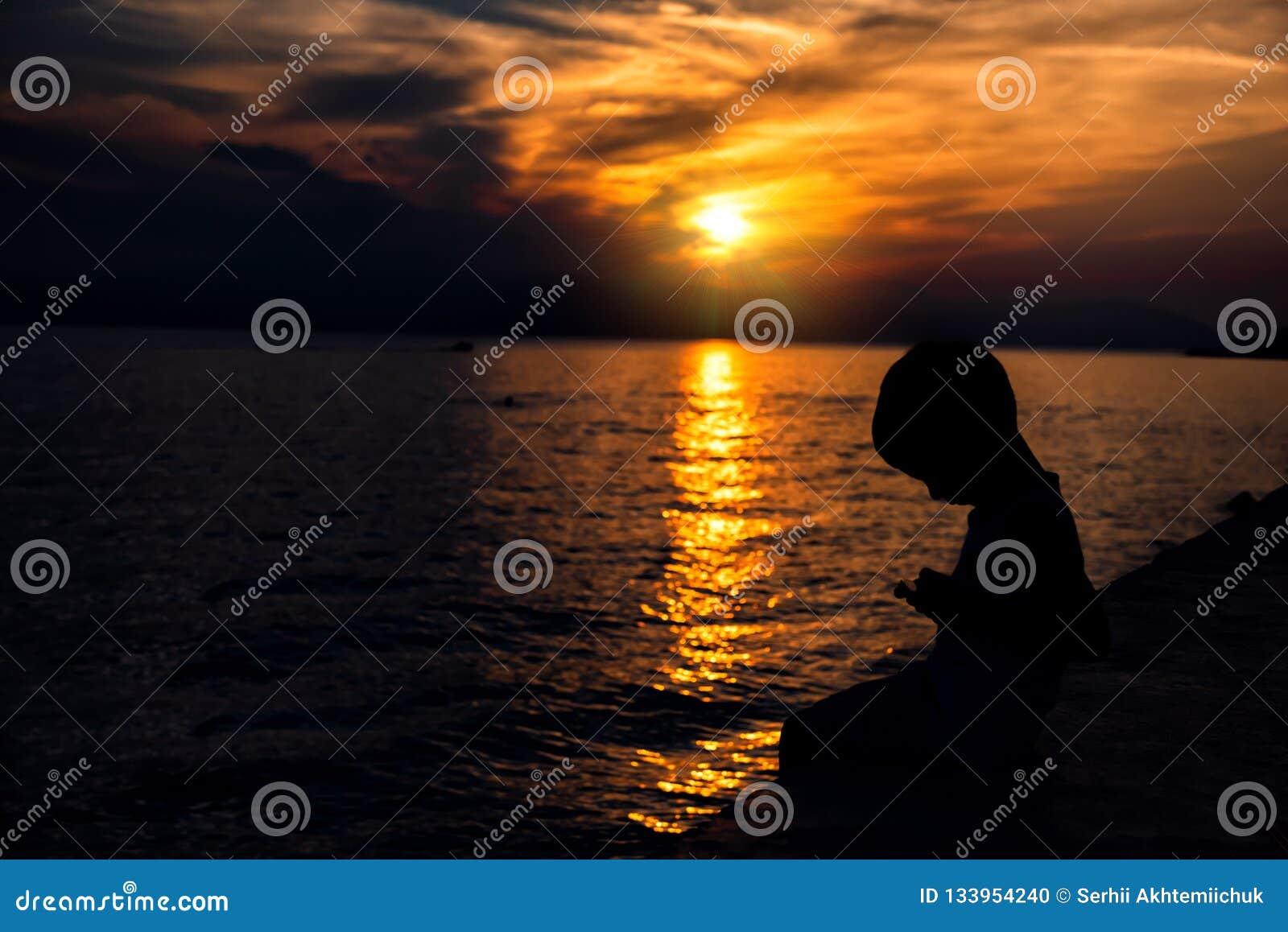 Ребенок смотрит в смартфон на предпосылке красивого захода солнца